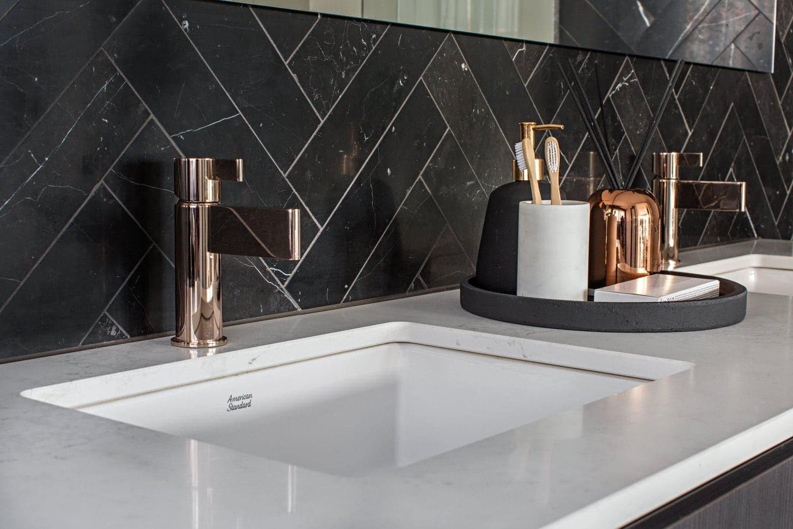 luxe bathroom with black marble herringbone tiles and copper tapware