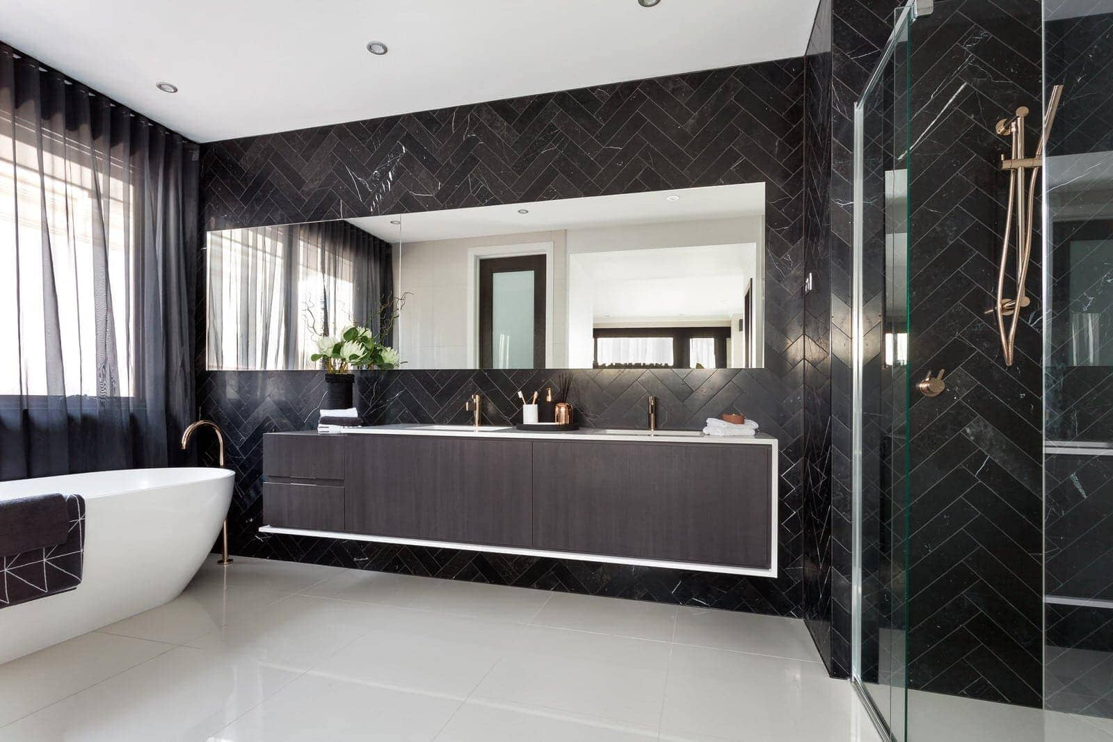 luxe bathroom with black marble herringbone tiles and floating vanity