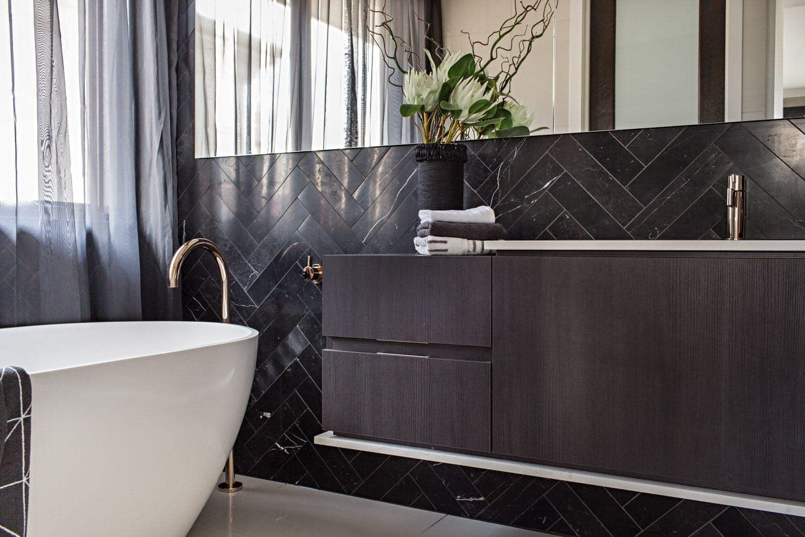luxe bathroom with black marble herringbone tiles and freestanding bath