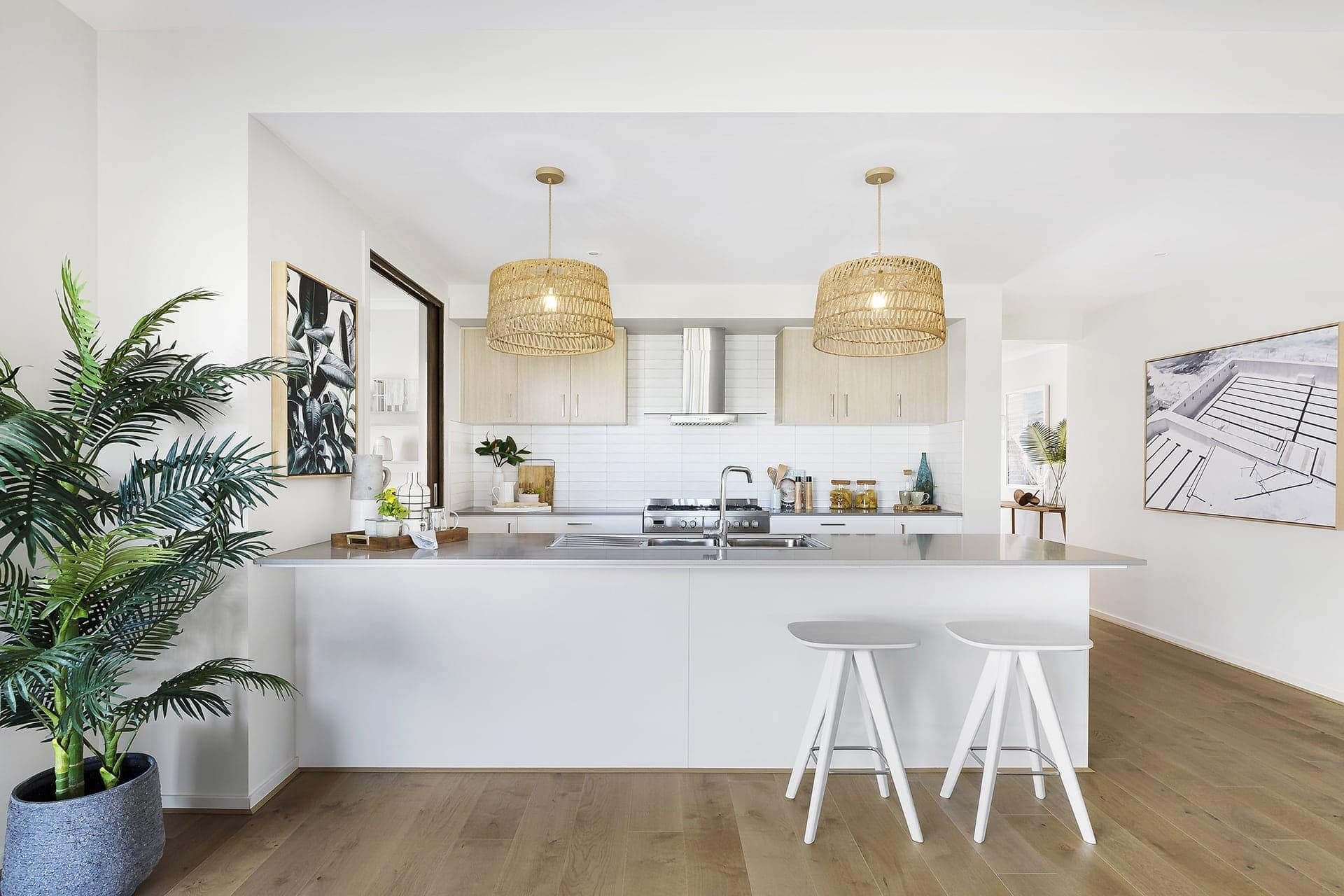 modern coastal kitchen with round rattan pendants and palm tree