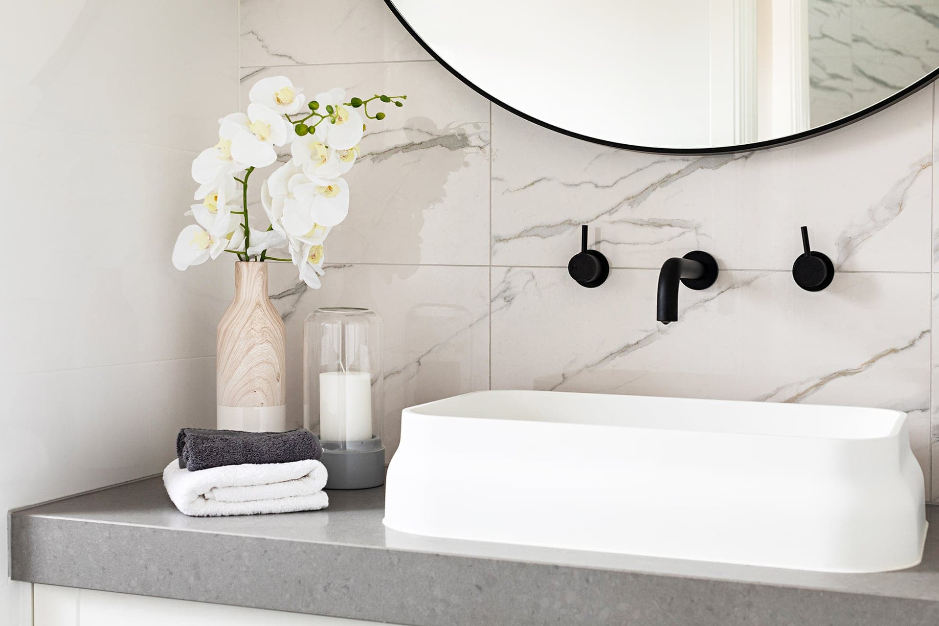 big w fake orchid in white bathroom with black taps