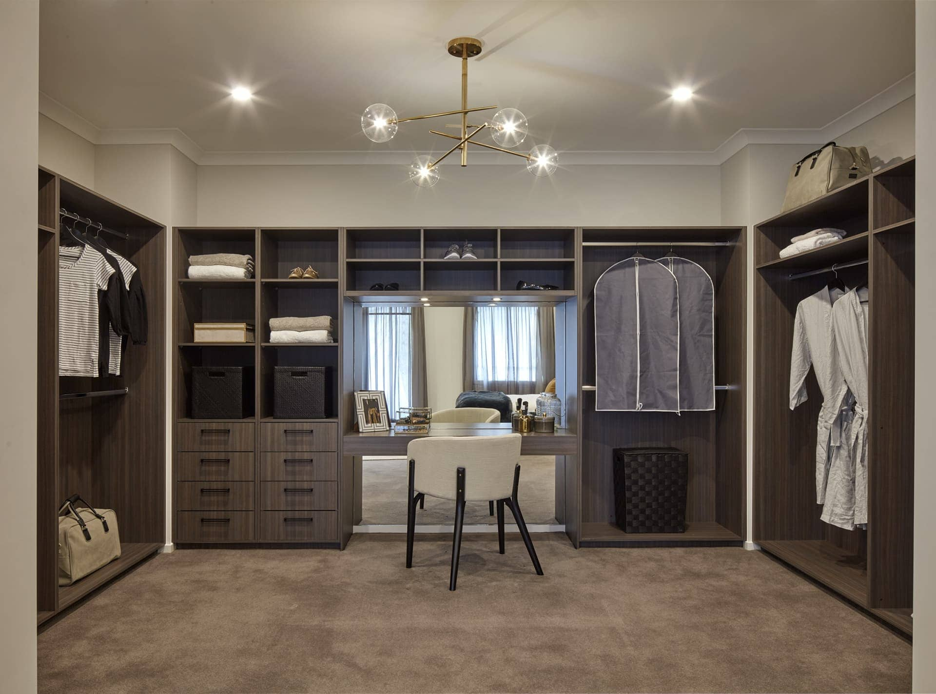 giant walk in robe with brown cabinetry and gold pendant light