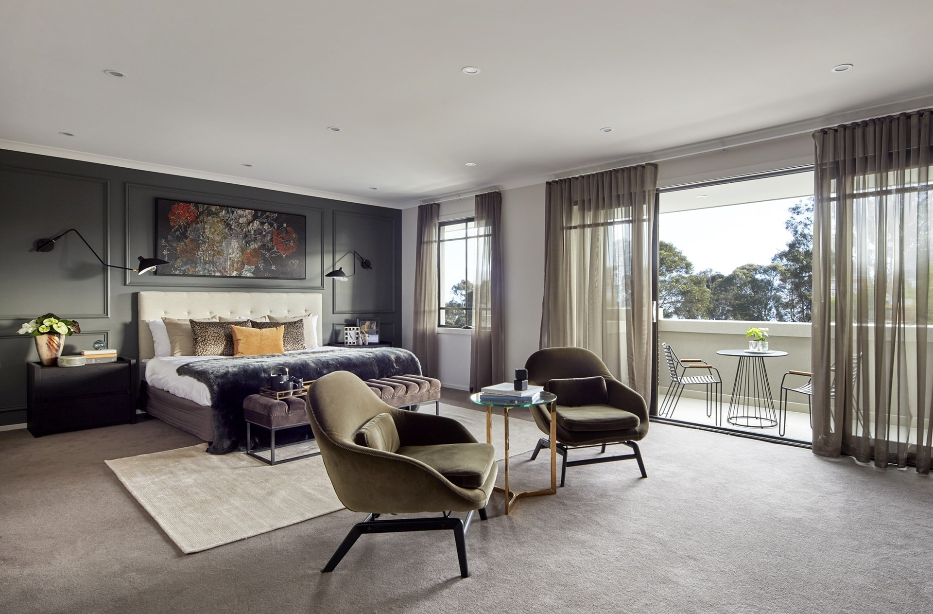 masculine master bedroom with wall moulding and velvet armchairs