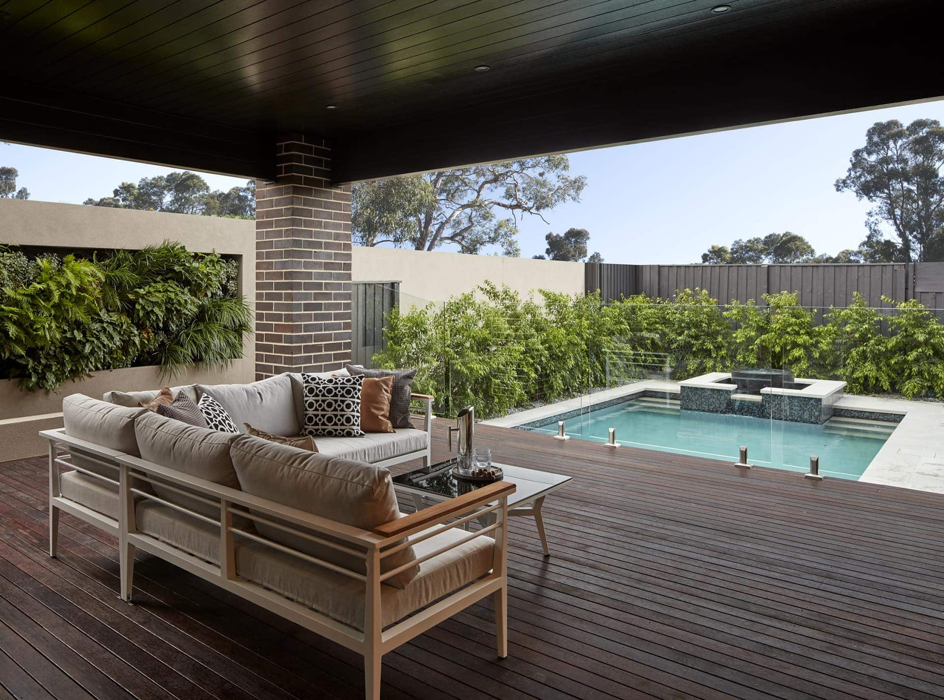 metricon outdoor area with timber decking and glass pool fence