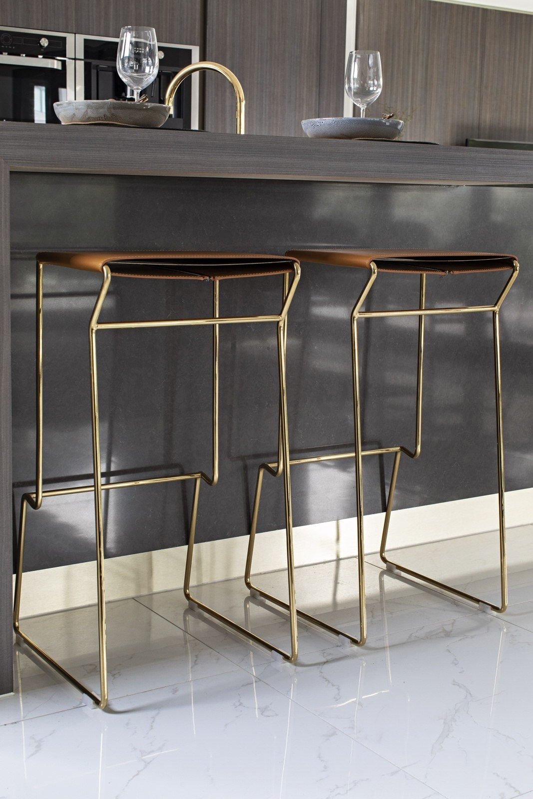 tan leather stools with gold legs in brown kitchen