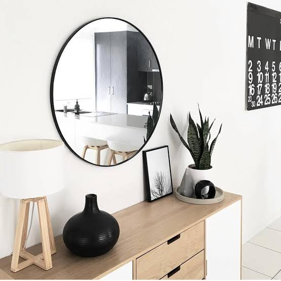 kmart large round mirror with black frame hanging above timber sideboard