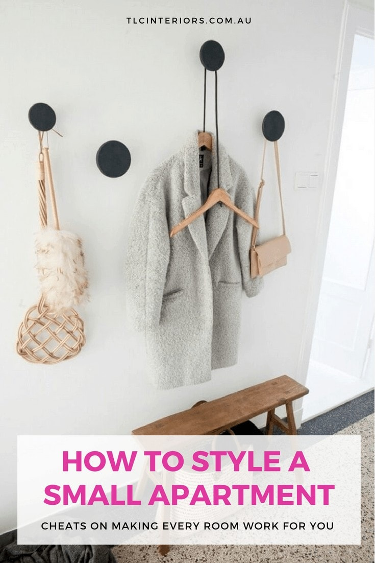 black round wall hooks in entryway with grey coat