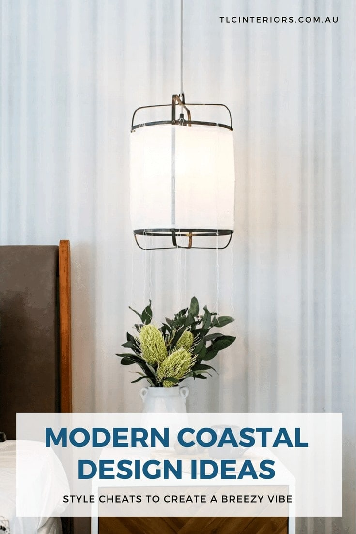 fabric pendant light hanging in coastal bedroom over timber bedside table