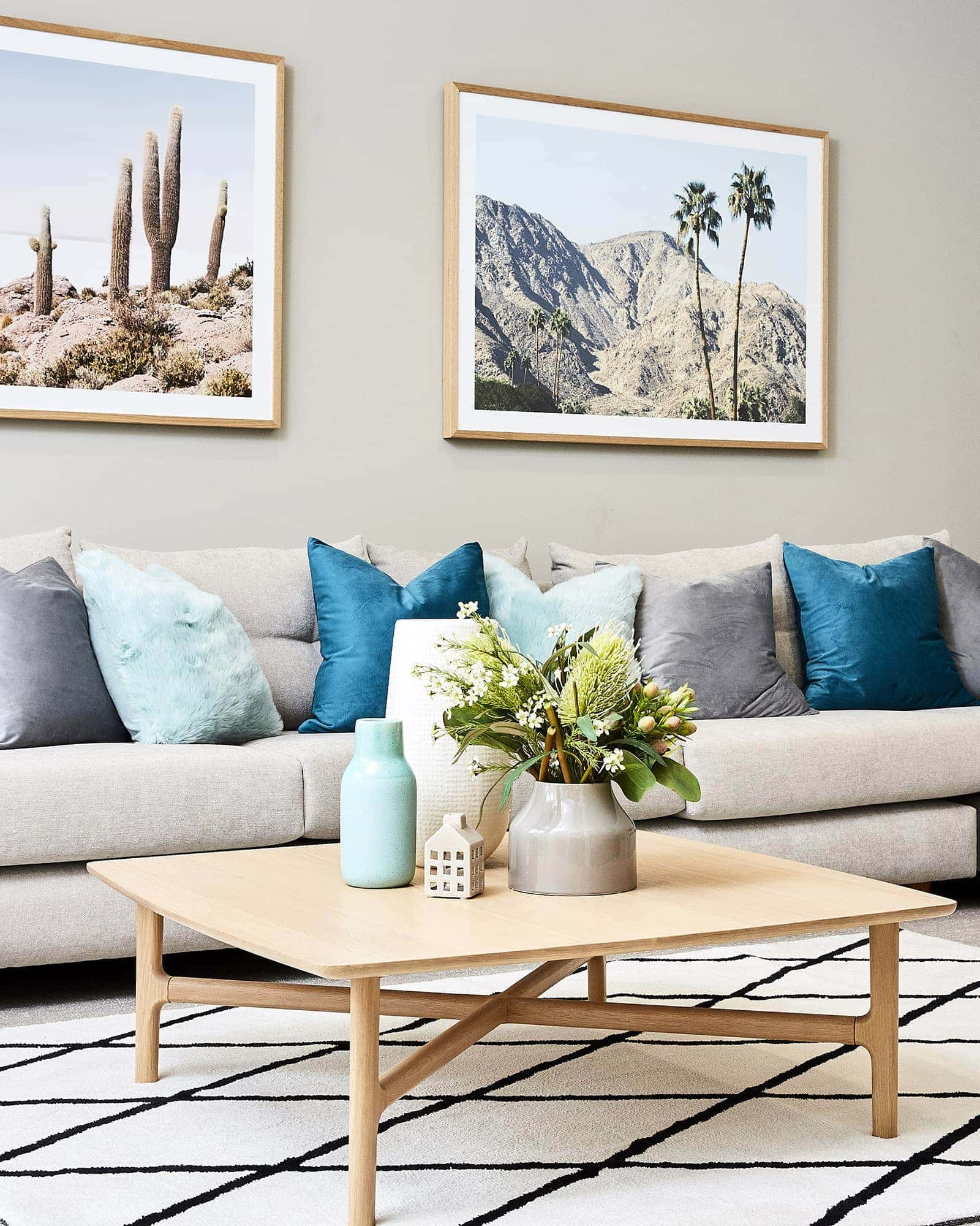 oak coffee table in living room with desert artwork and teal cushions from lorraine lea spring decorating