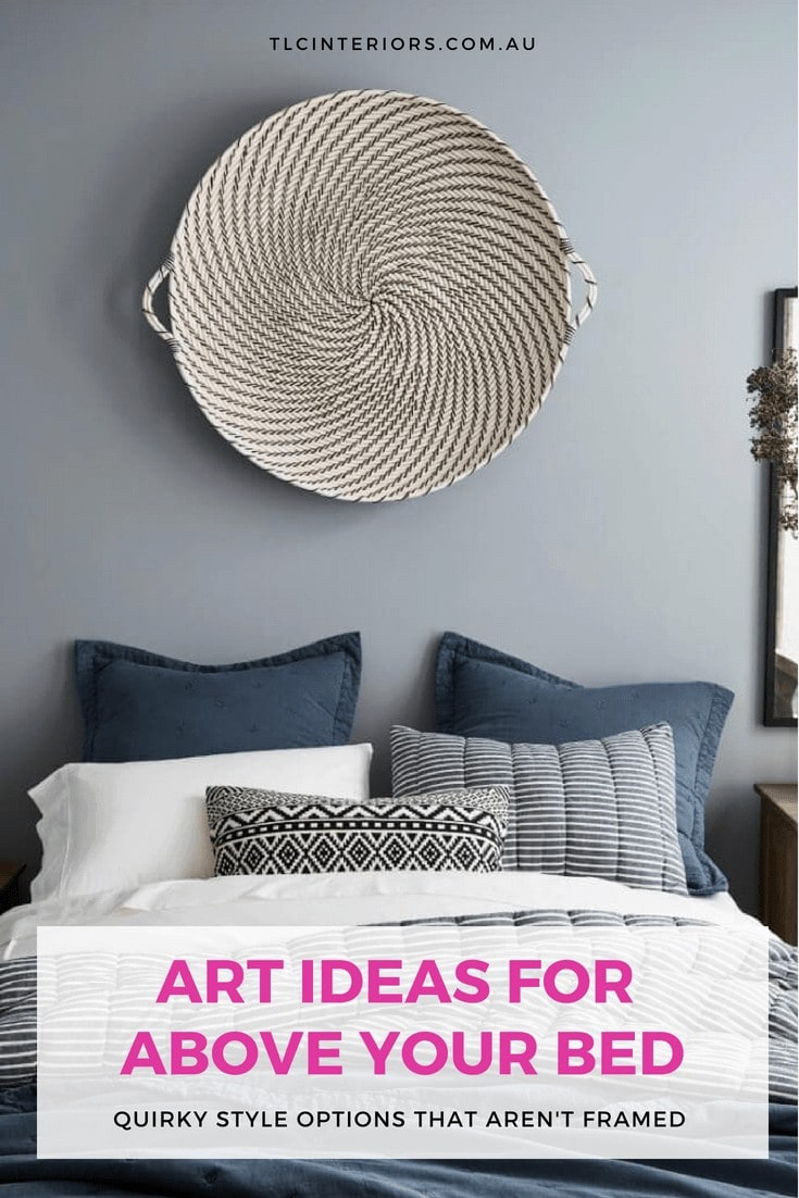 round tray hanging on blue wall above bed from pottery barn
