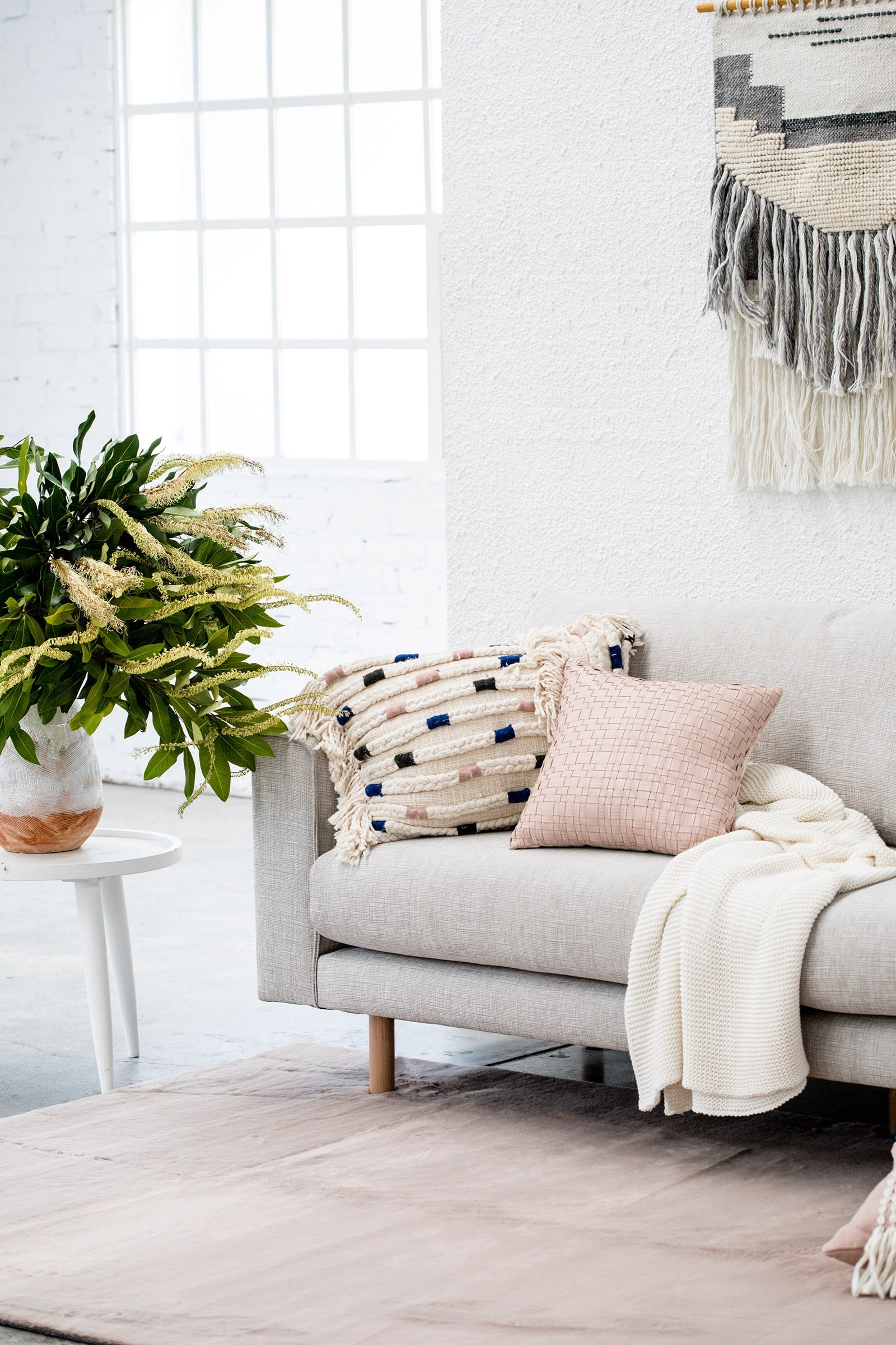 oz design light grey sofa with bohemian cushions and australian natives in vase