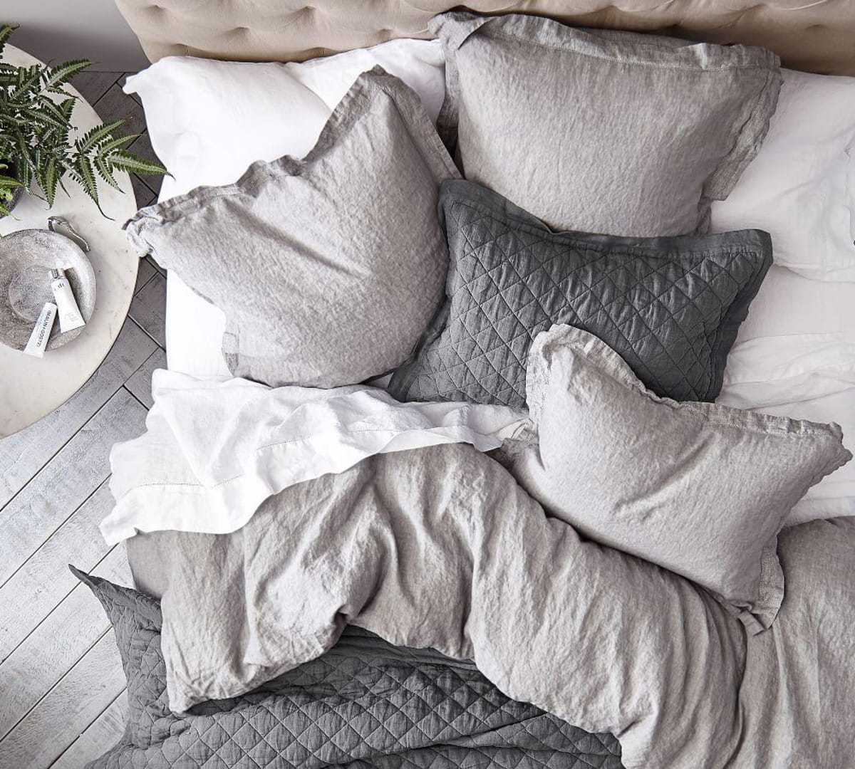 quilted grey bed linen flatlay with round side table in guest bedroom