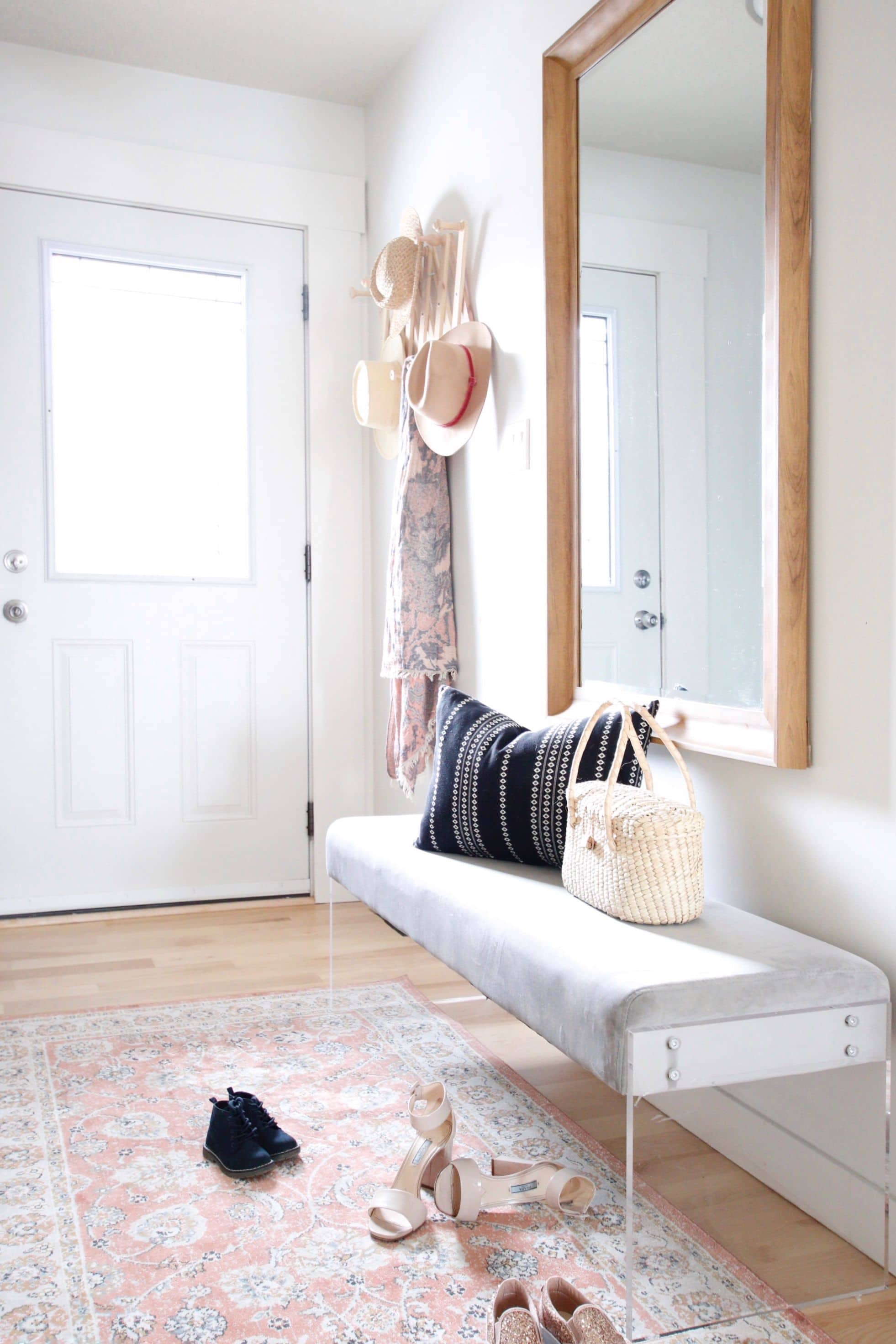 decorating a small entryway with large mirror and bench seat and floor runner