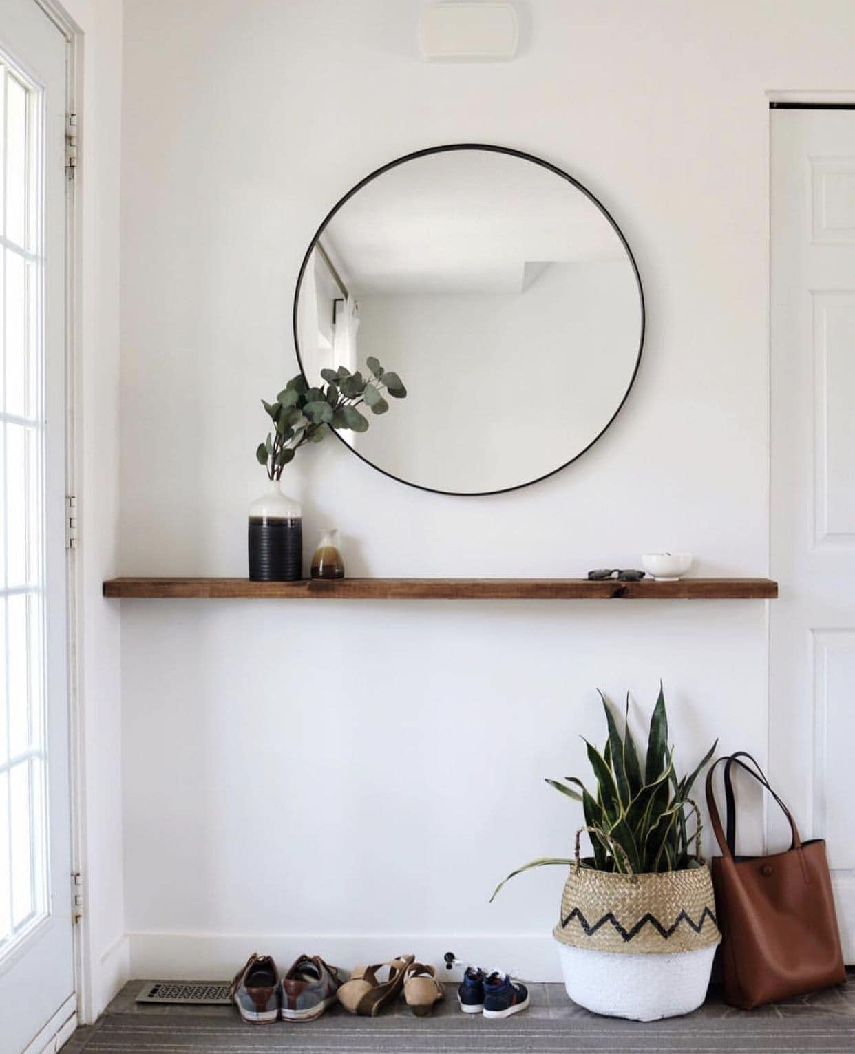 round black mirror in entryway above floating timber shelf small entryway decorating ideas