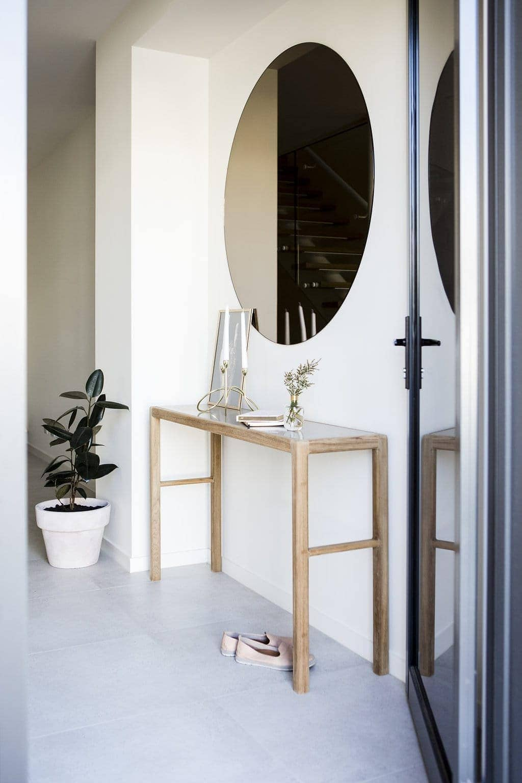 round entryway mirror above slimline entry table by h and g designs