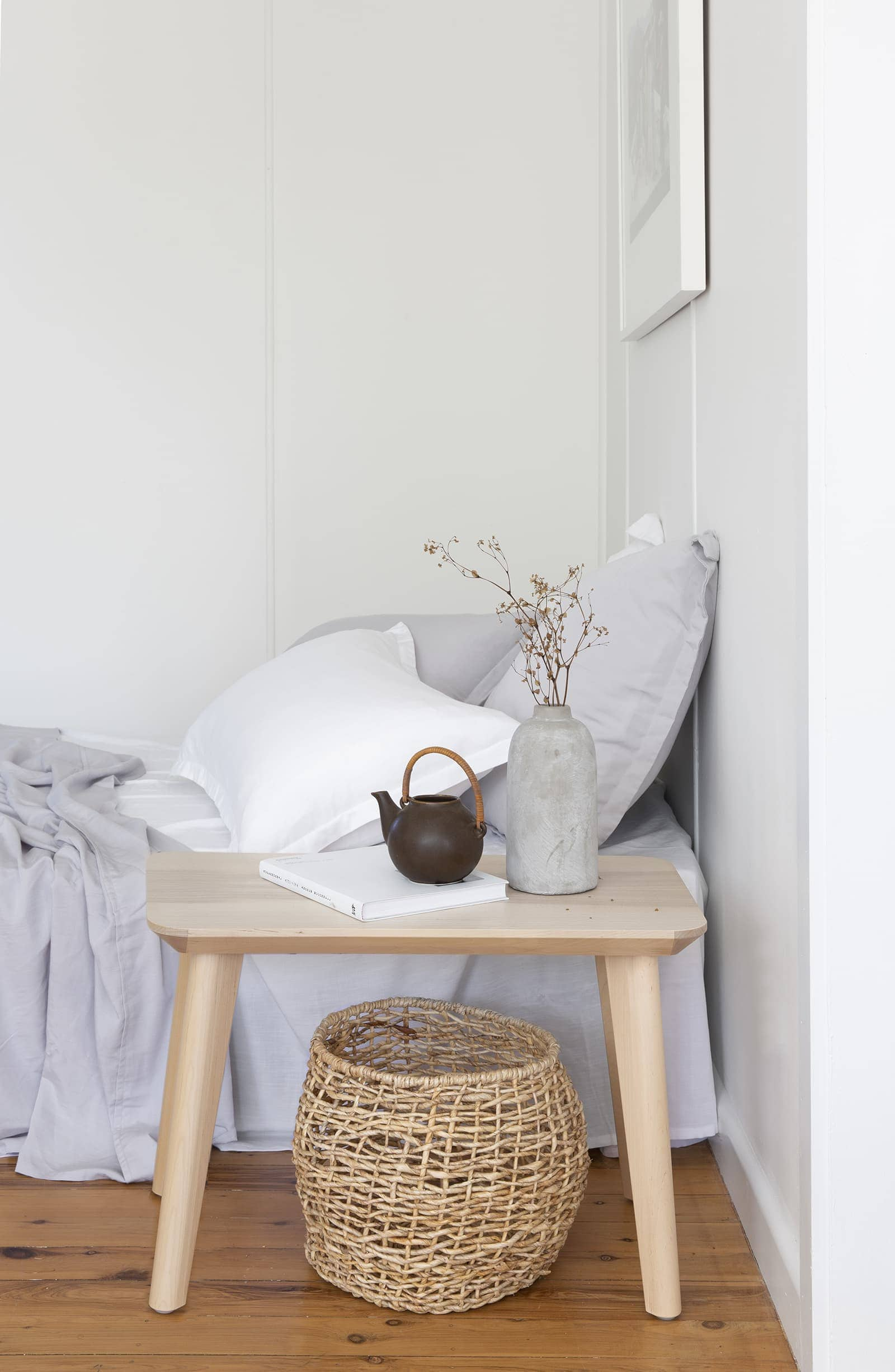 bright white bedroom with bamboo bedding and light timber floors