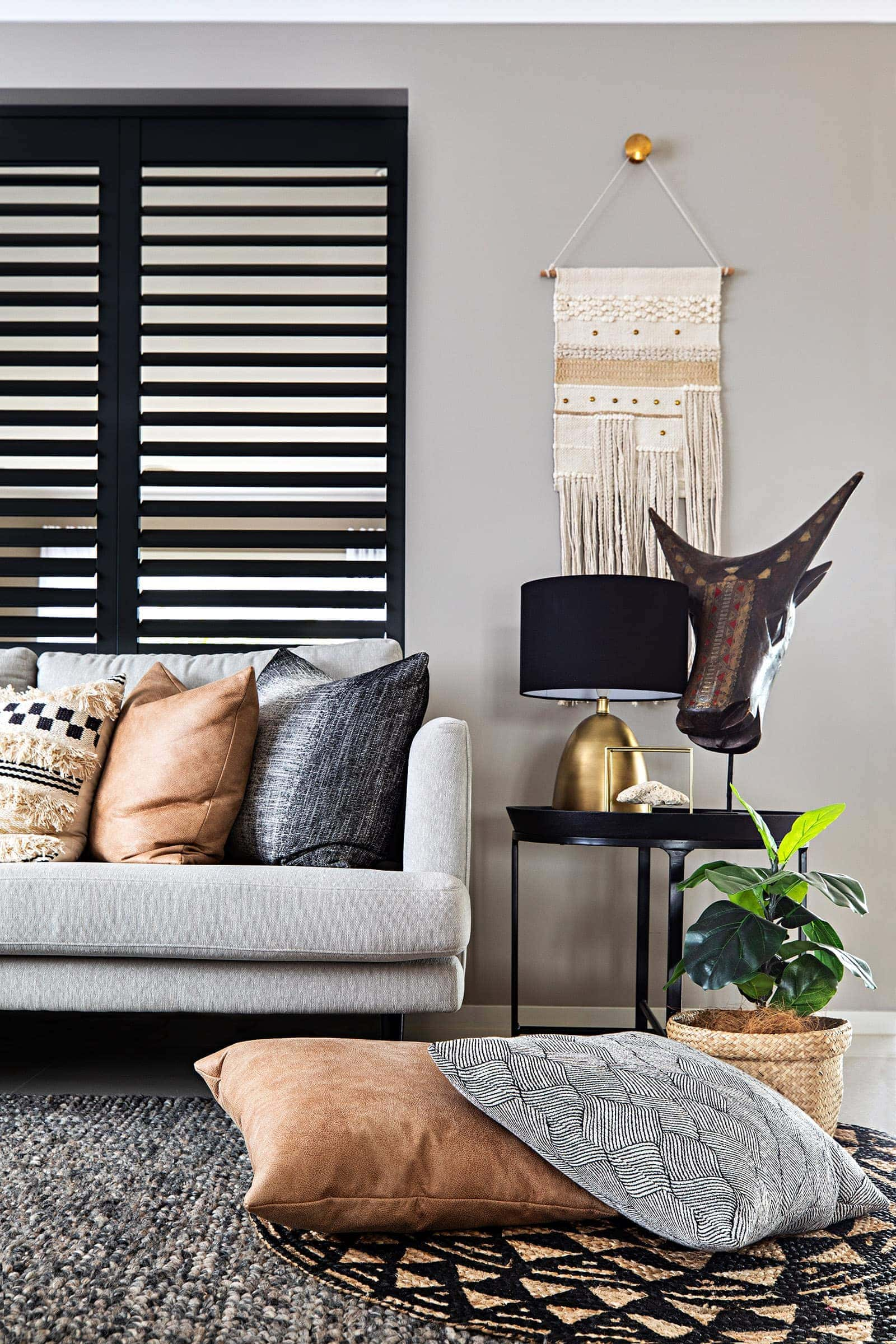dark bohemian living room with tan leather cushions and macrame wall hanging