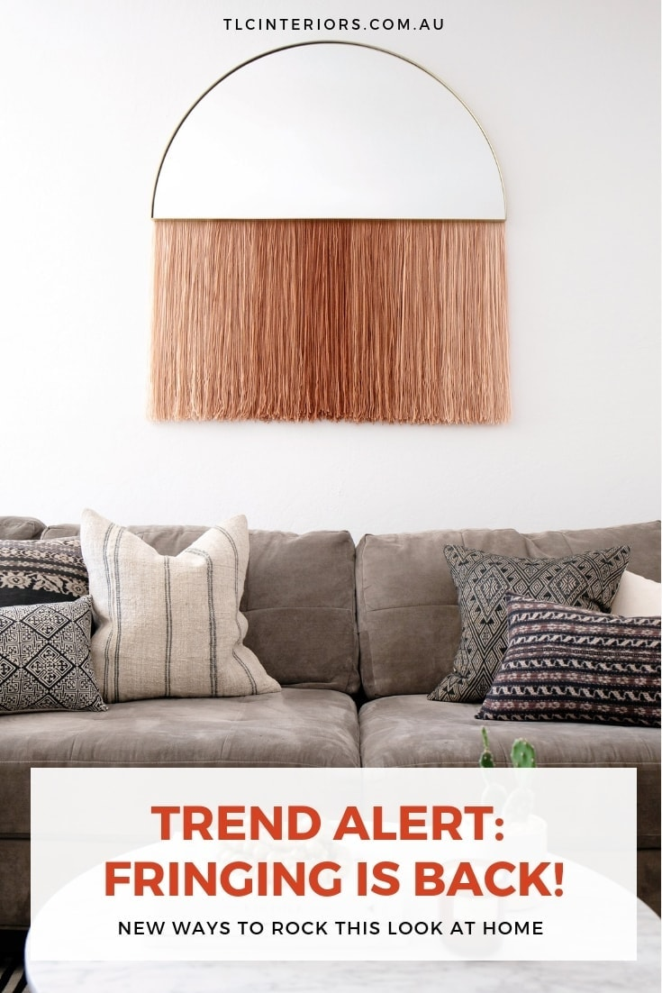 fringe mirror with blush tassels hanging in living room with white walls and grey sofa