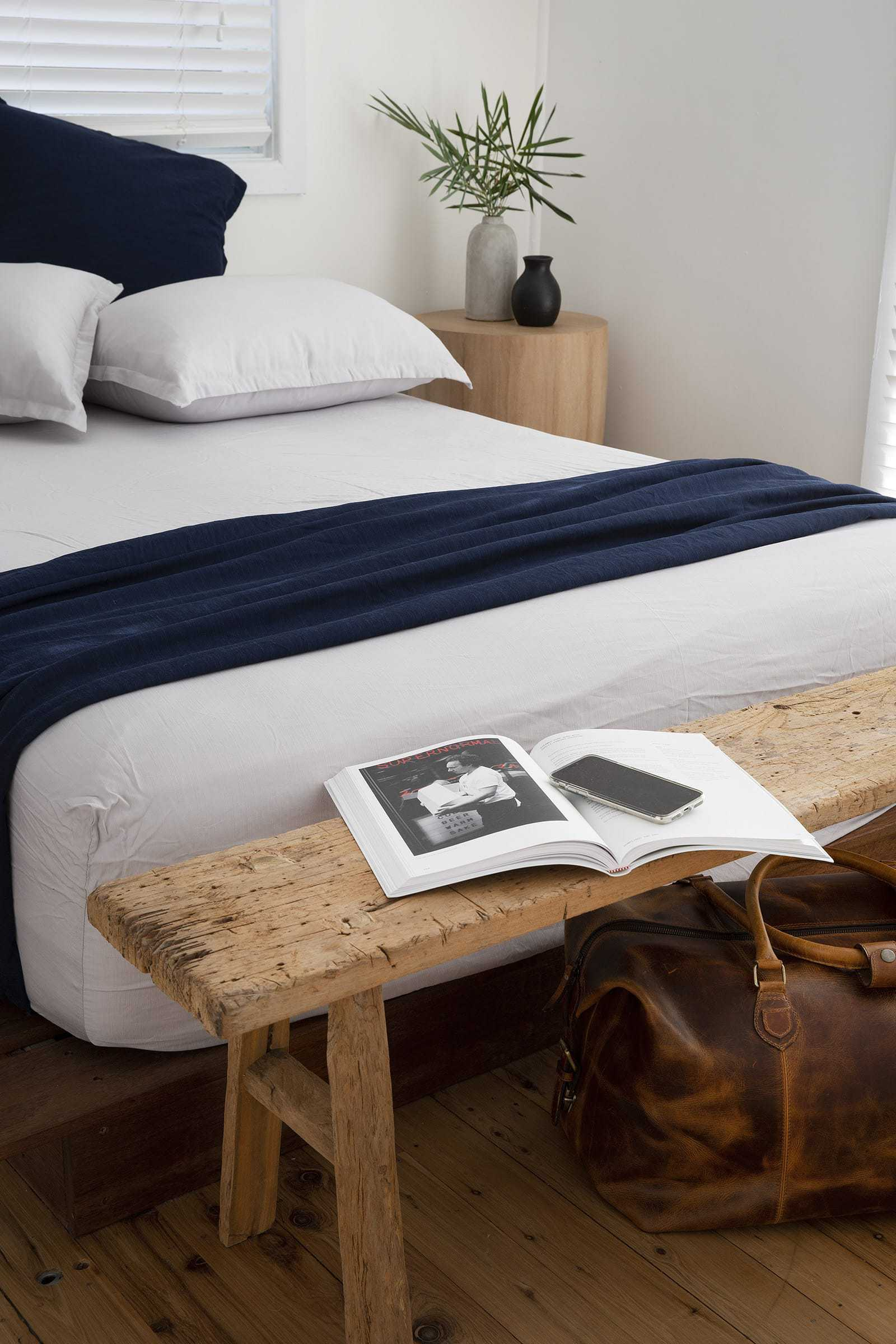 navy and white loom living bamboo bedding in bedroom with timber floors and bench seat at end of bed