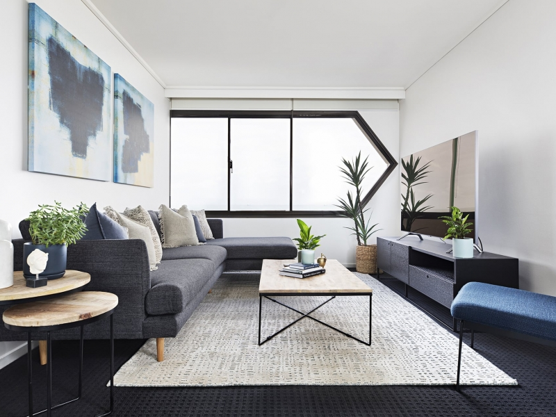dark coastal living room with dark grey carpet and black window frames