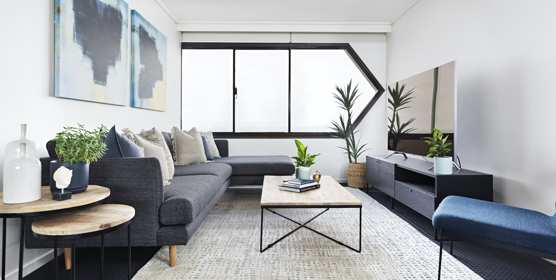 moody coastal interior design living room with grey sofa blue armchair st kilda apartment