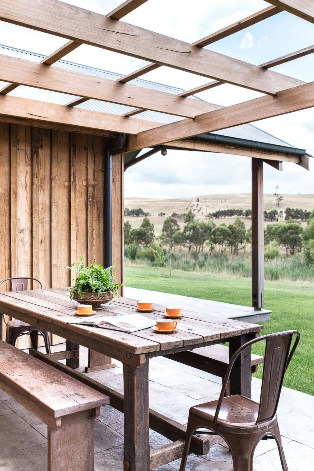 bendooley estate review exterior log cabin industrial style outdoor table on back patio