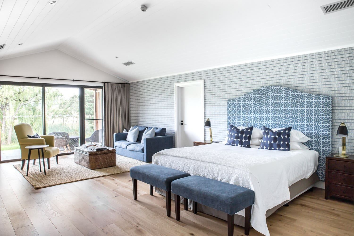 bendooley estate studio bedroom with wallpaper and upholstered headboard and timber flooring
