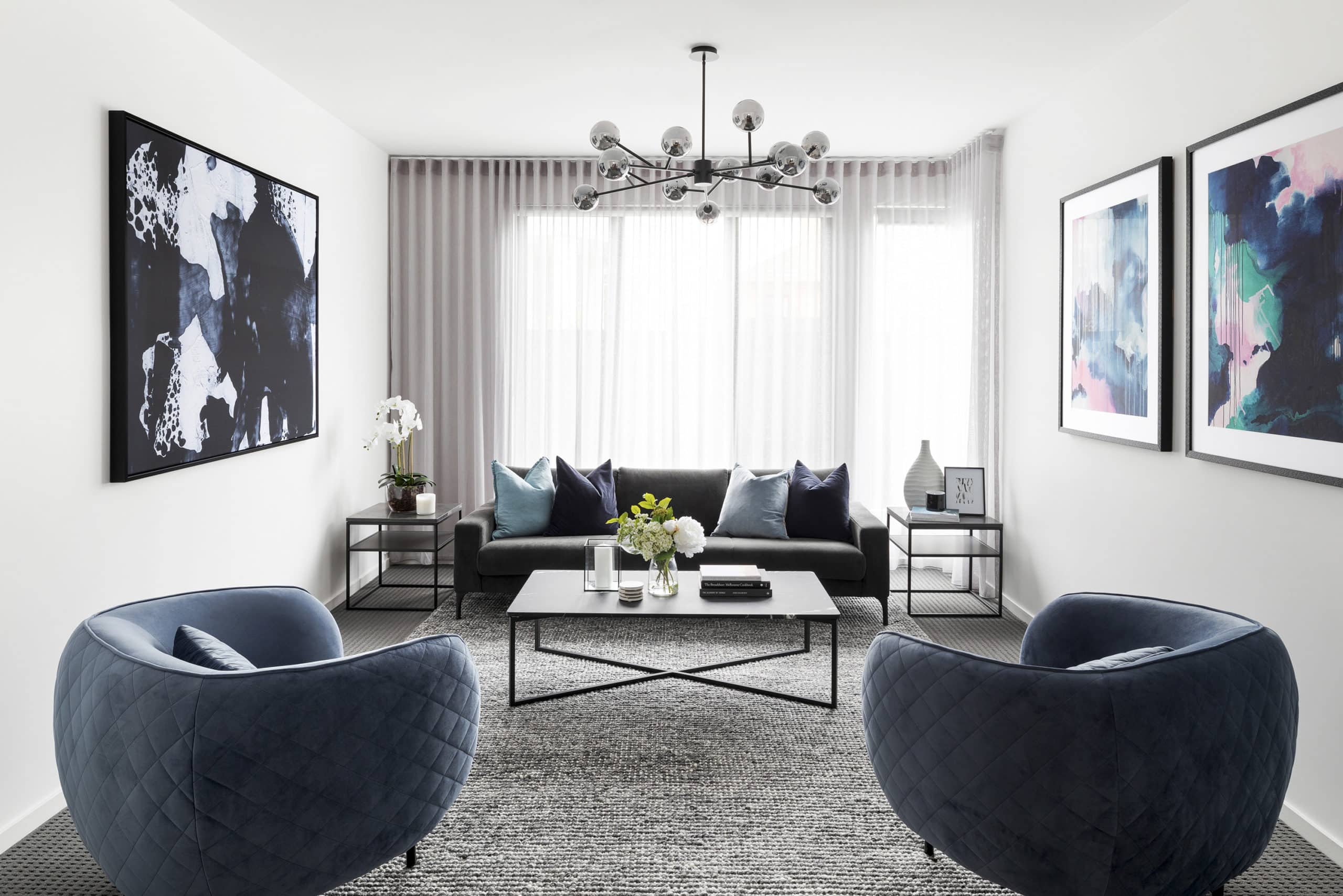 contemporary luxe living room with blue velvet armchairs and black marble coffee table