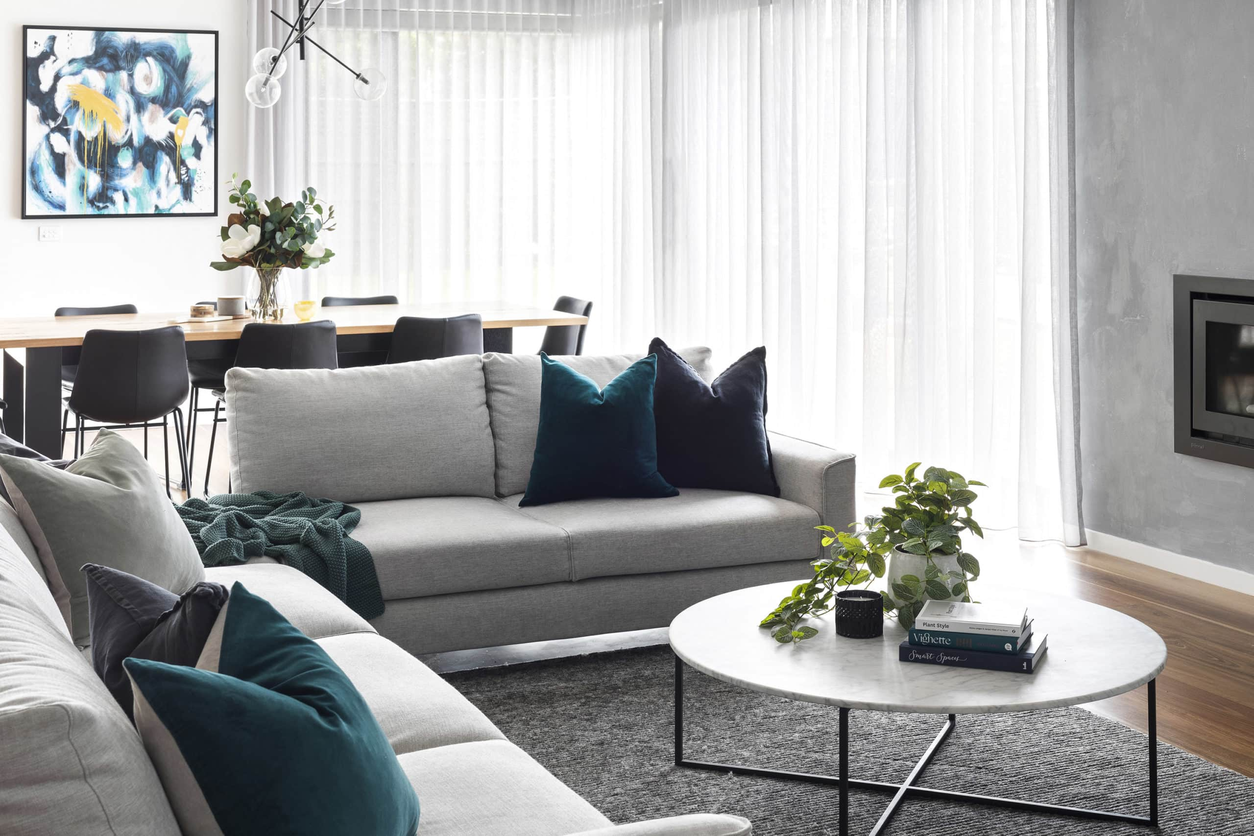 contemporary luxe living room with grey king living sofa and round marble coffee table