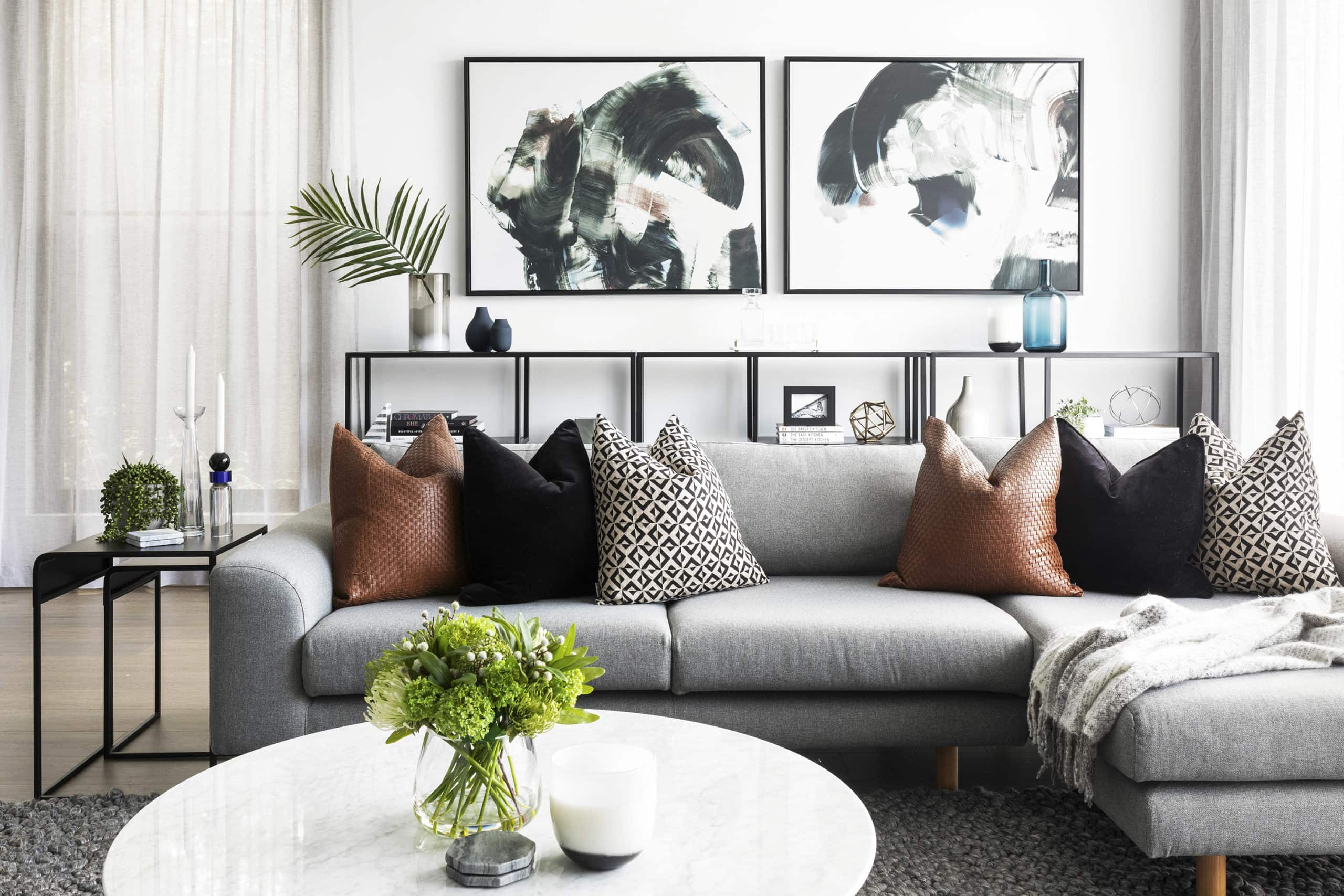 grey sofa with tan cushions and round marble coffee table in contemporary luxe living room