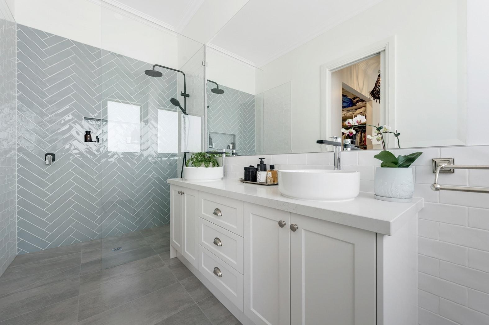 hamptons bathroom with white shaker vanity and blue herringbone tile on shower wall black tapware