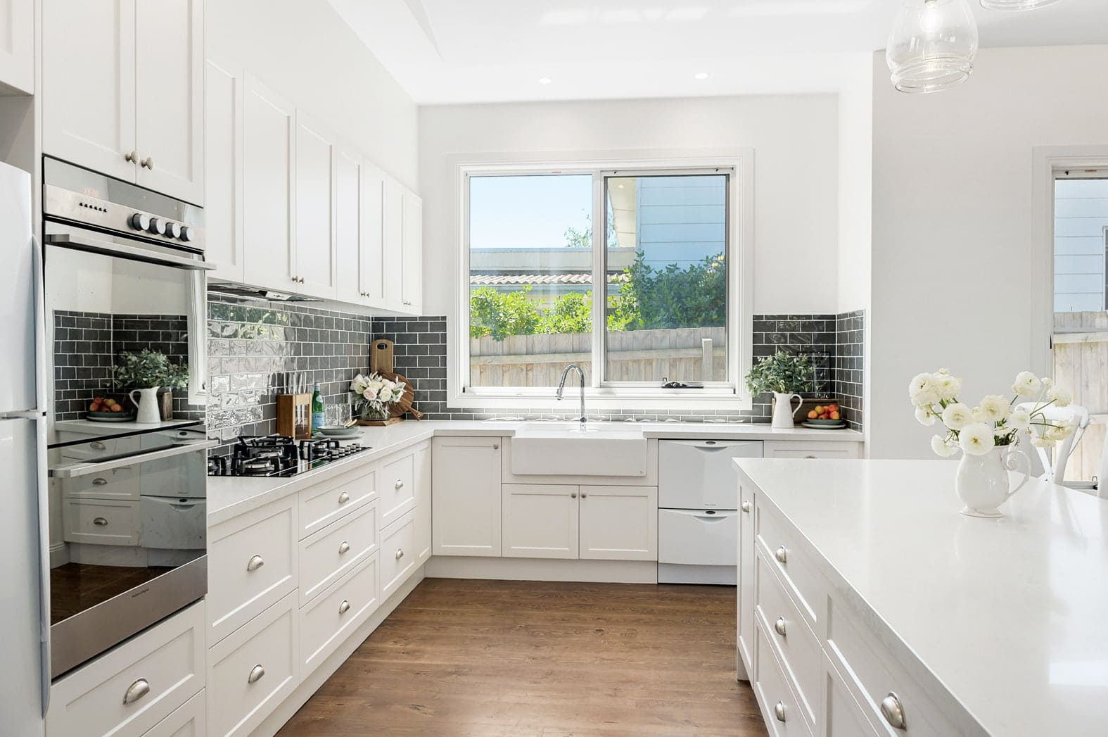 hamptons kitchen with butlers sink and white shaker cabinetry and blue splashback tiles in subway pattern