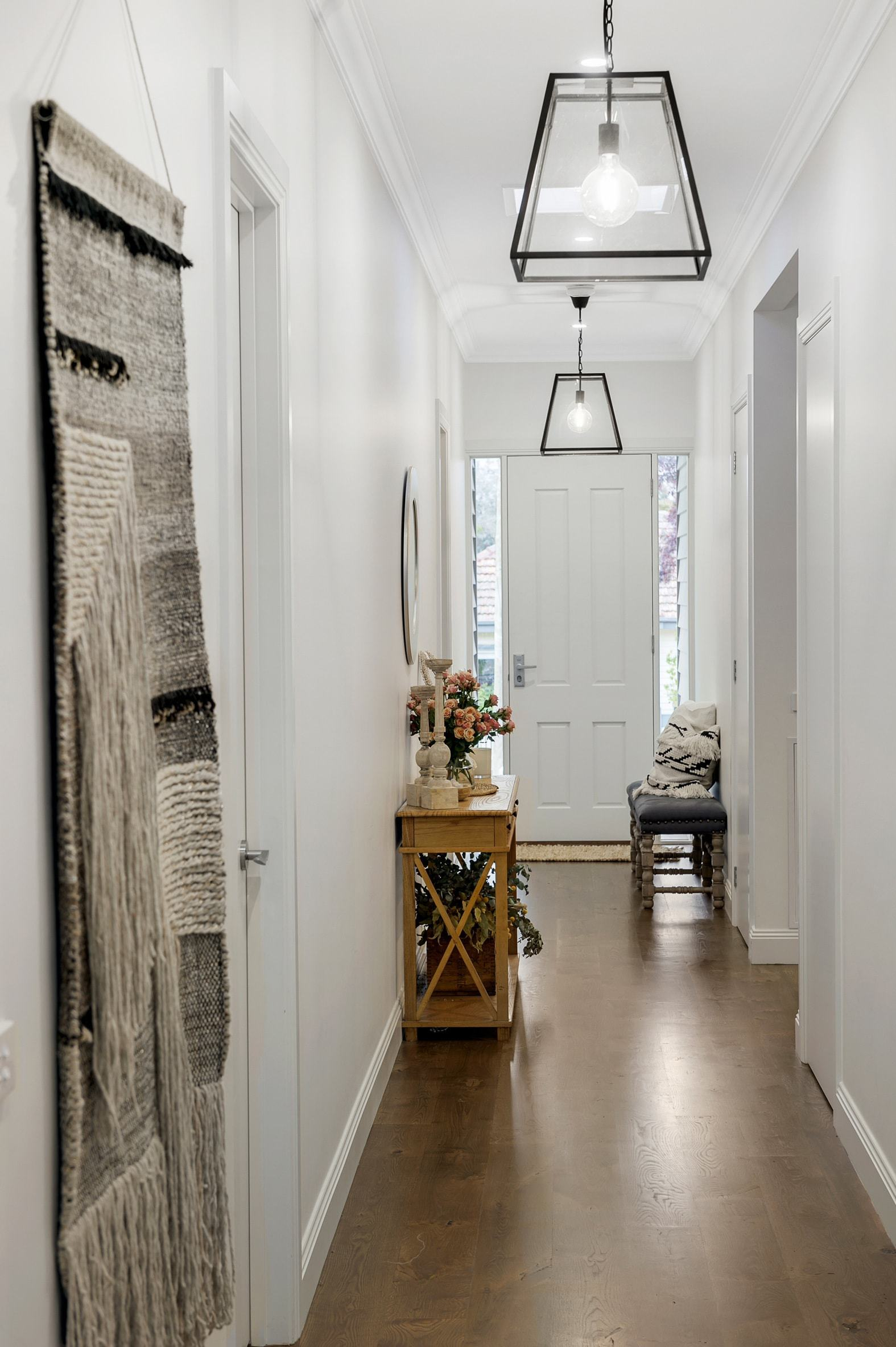 hamptons style entry with black industrial pendant lights and macrame wall hanging