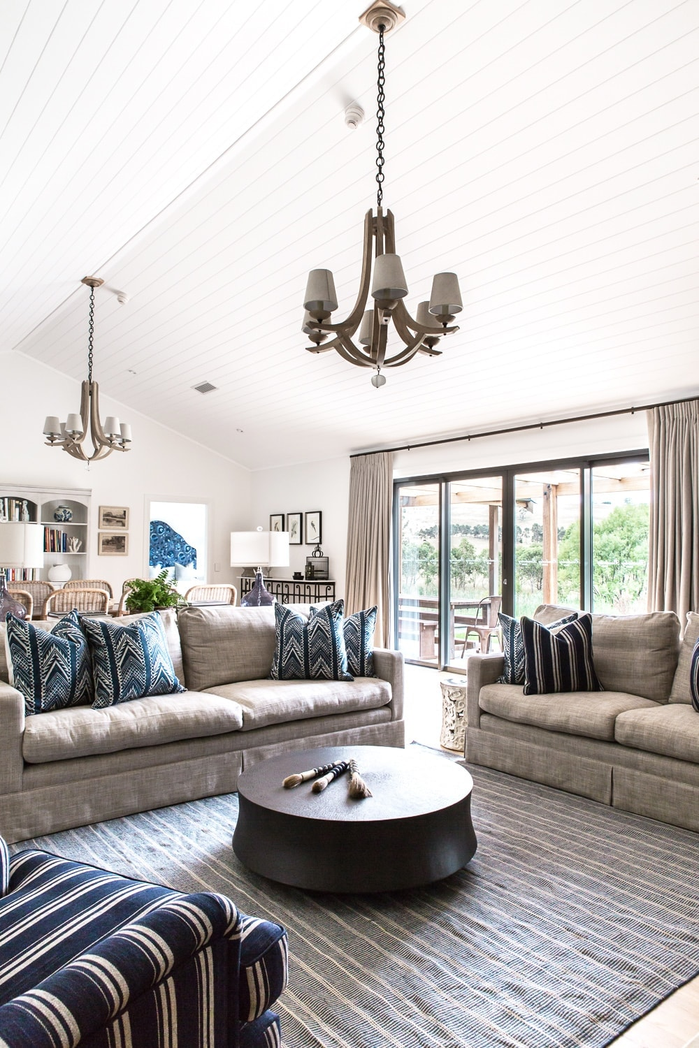 hamptons style open plan living and dining room with white panel ceiling and light brown timber floorboards