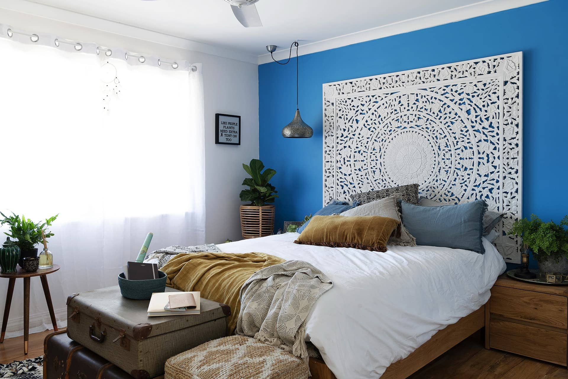 house rules 2019 eliza and mikaela boho bedroom with blue feature wall and suitcases as side tables