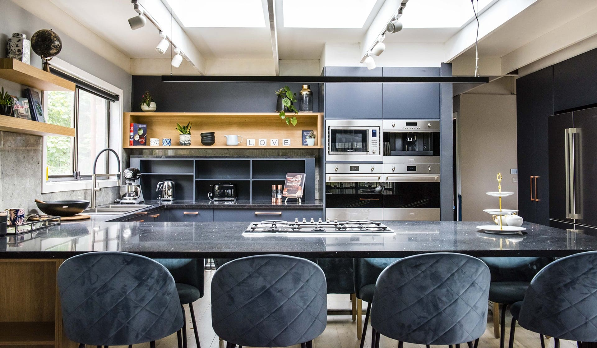 house rules 2019 pete and courtney kitchen with black countertop and blue cabinets