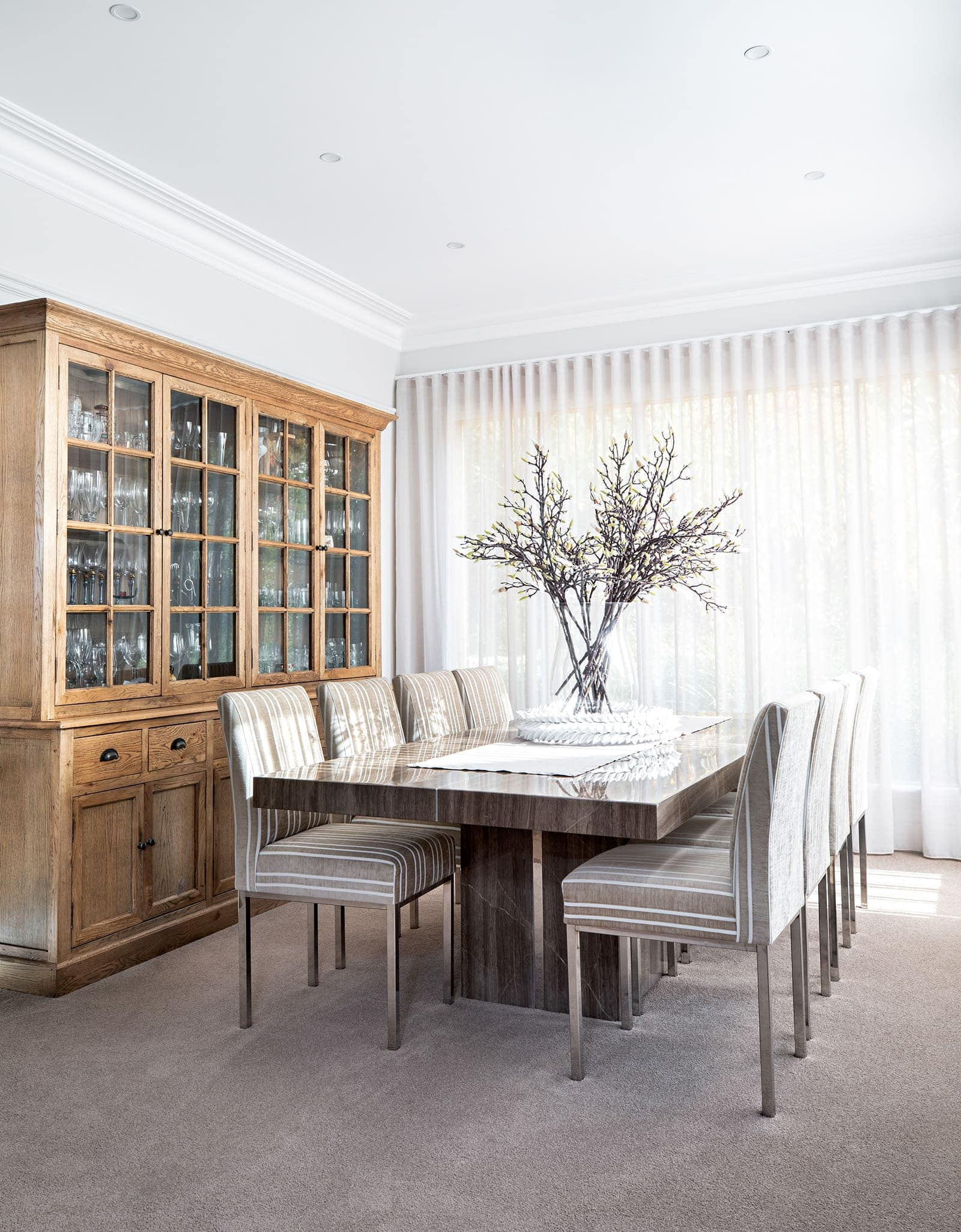 modern provincial dining room with provincial hutch and large vase of flower stems