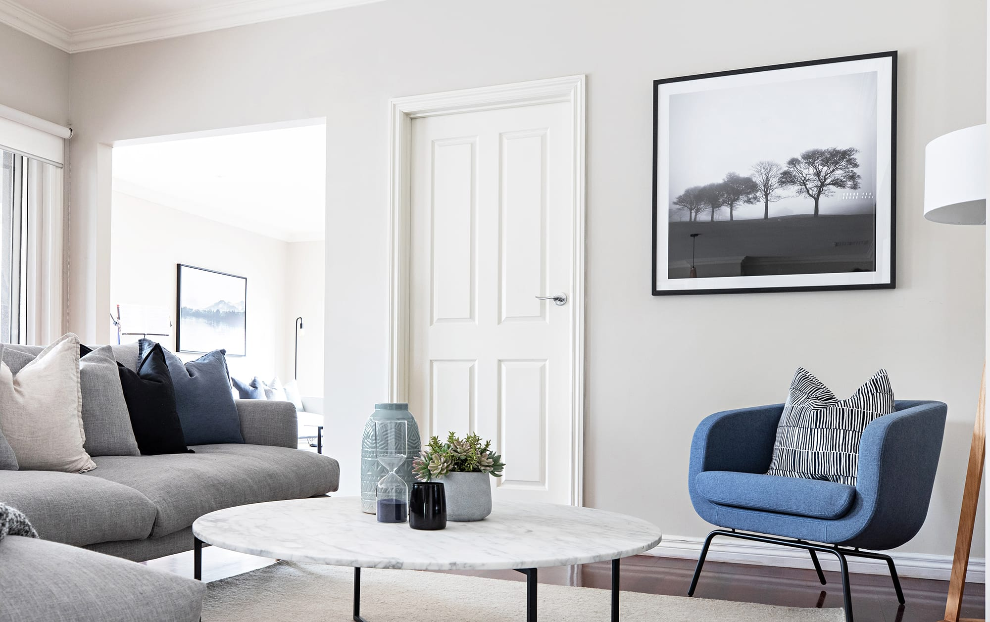 scandi living room with grey sofa and blue armchair