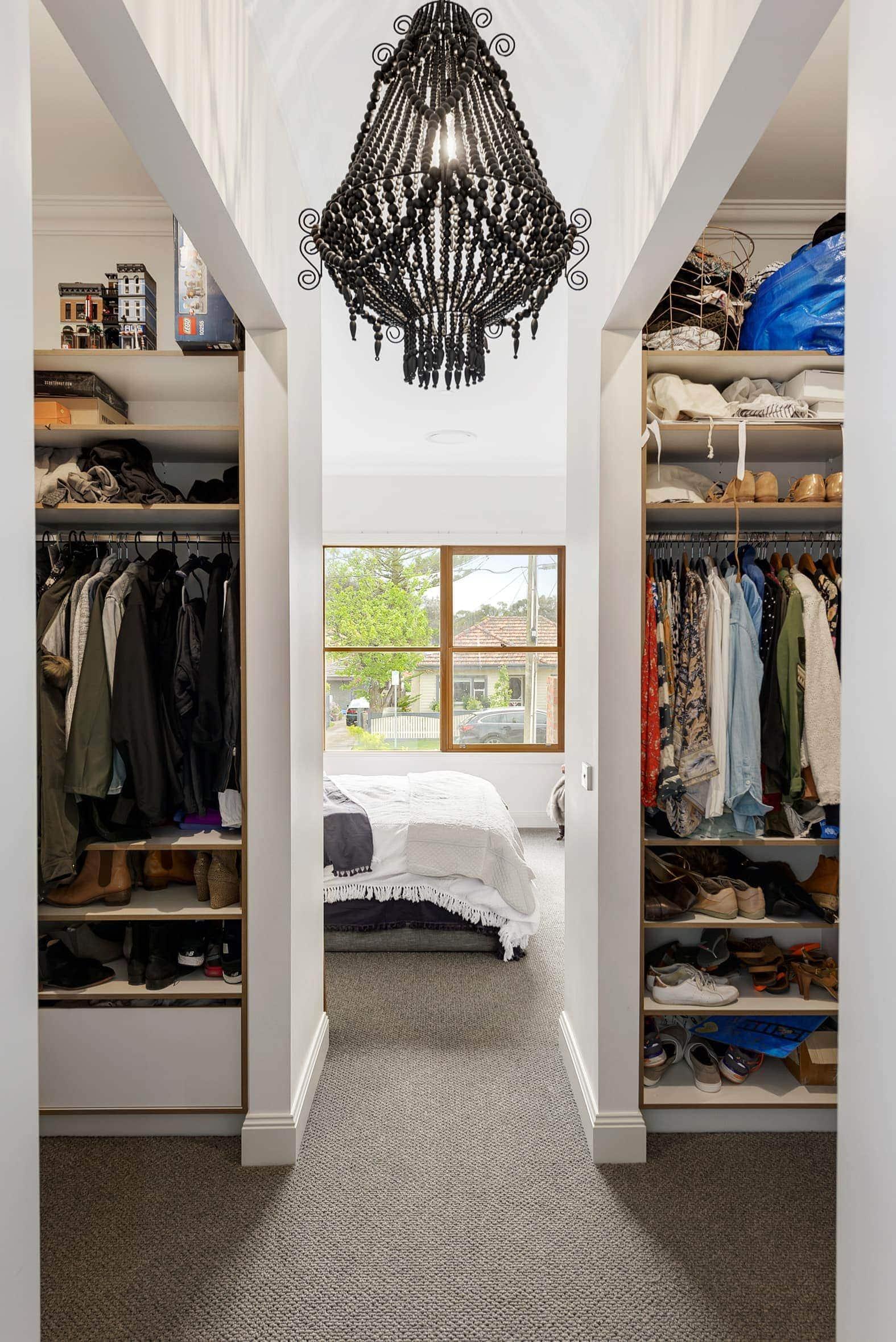 walk in wardrobe with black clay pendant light and grey carpet