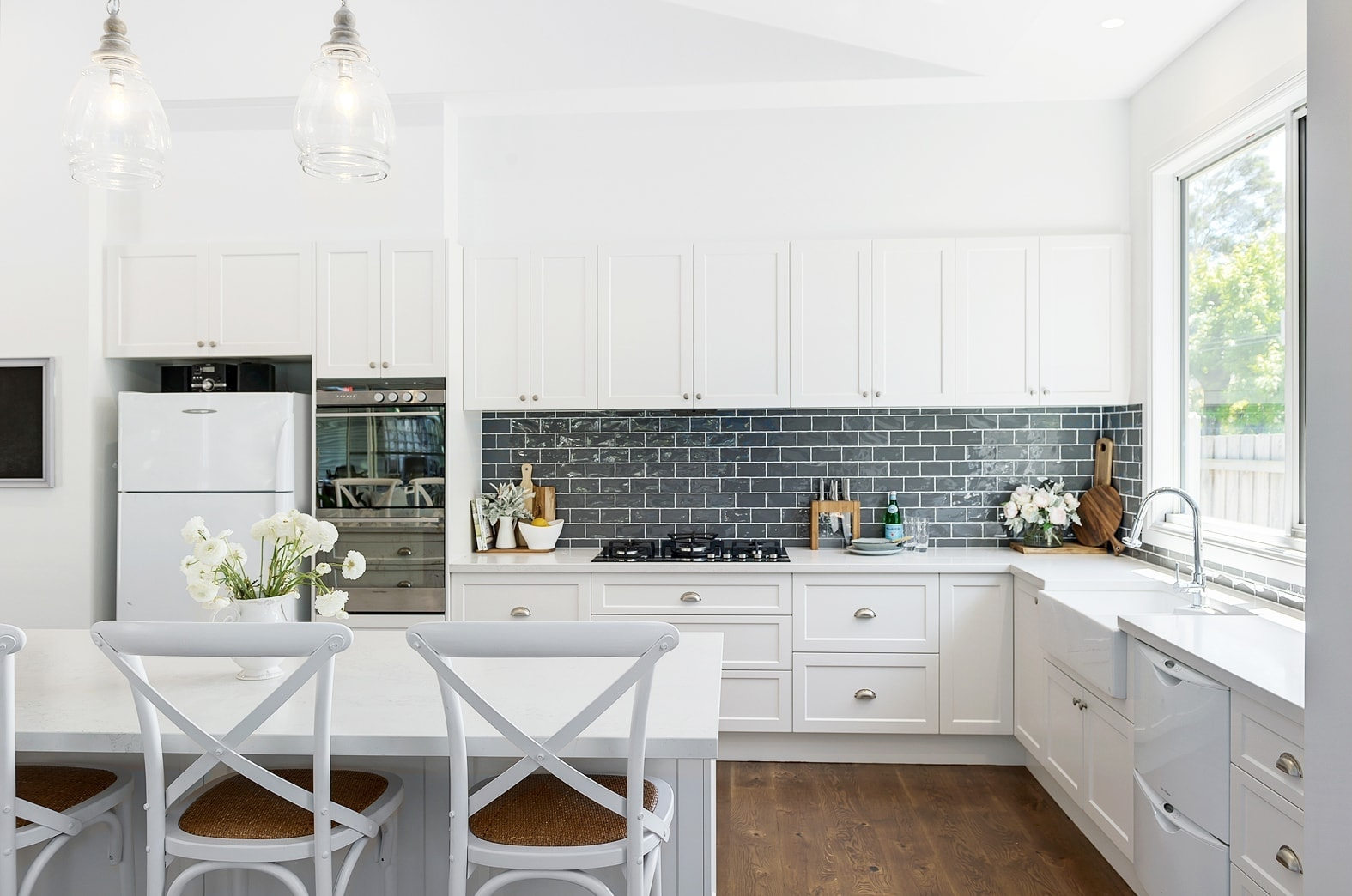 white hamptons kitchen with blue splashback tiles and shaker cabinetry door profile