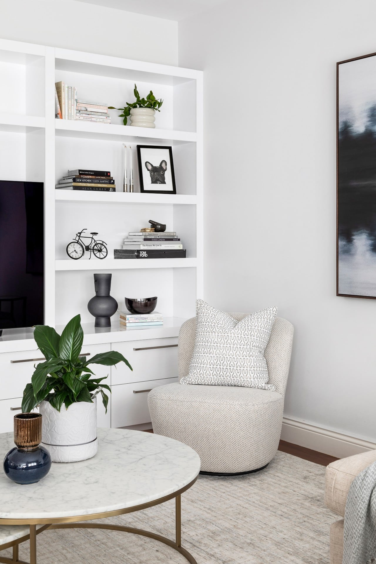 chic monochromatic living room white shelf styled with black decor white swivel armchair