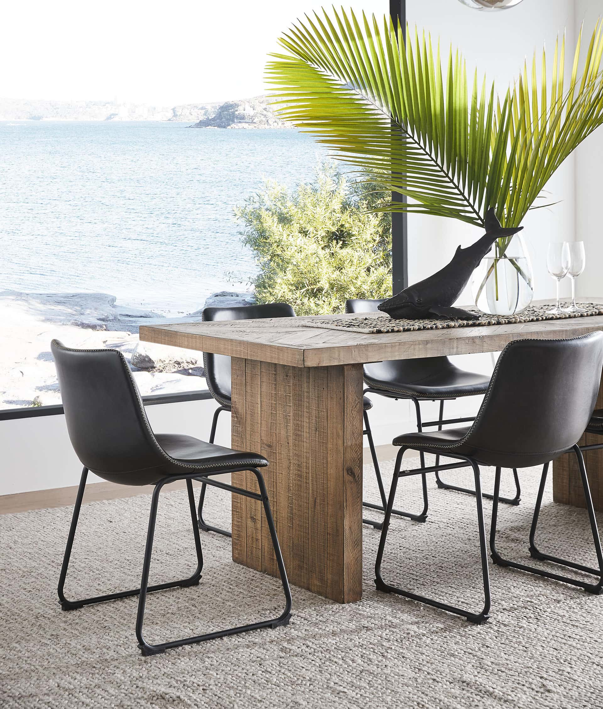 coastal dining table with black leather armchairs by window with view of the sea