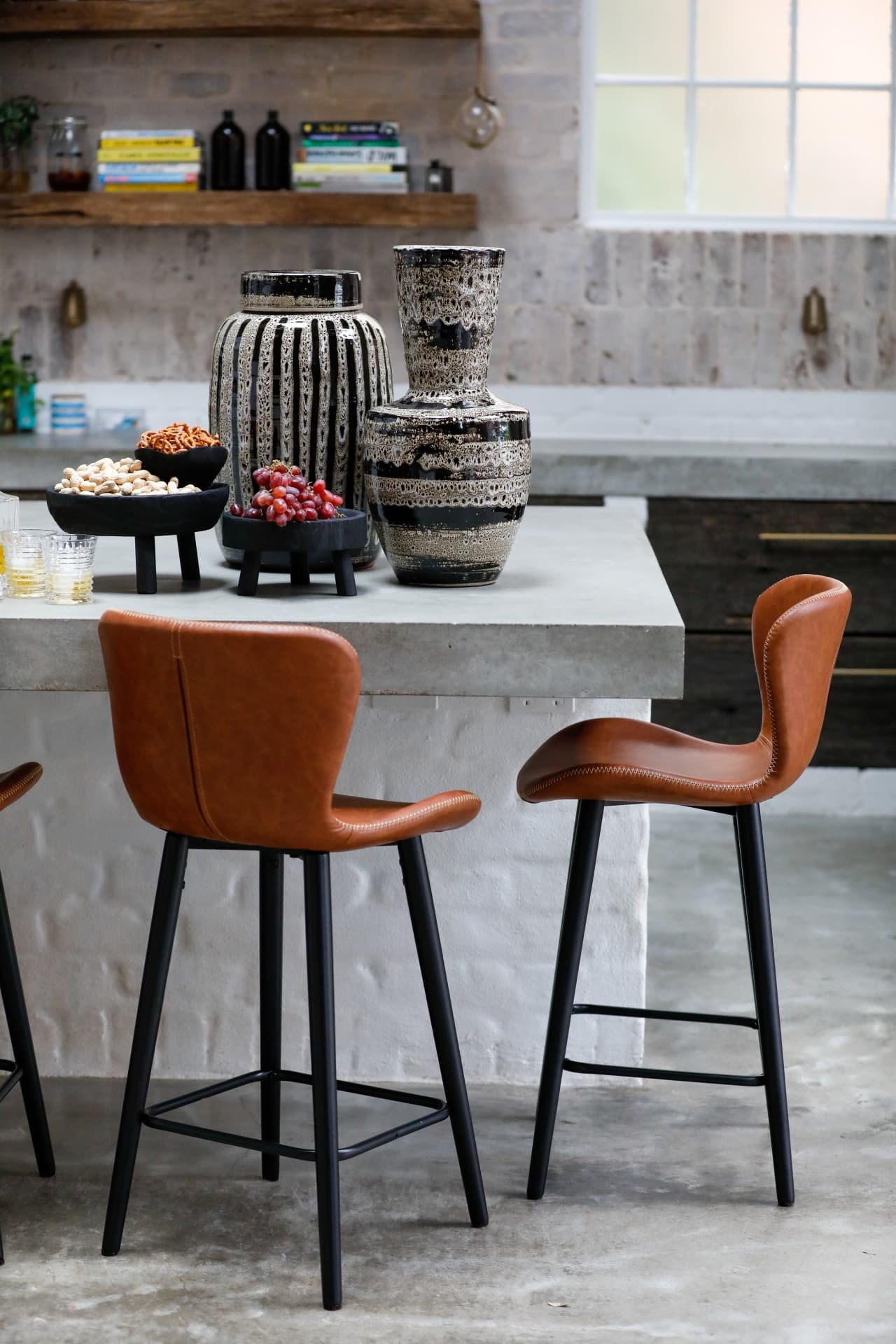 tan leather bench stools in industrial warehouse kitchen with ceramic vases