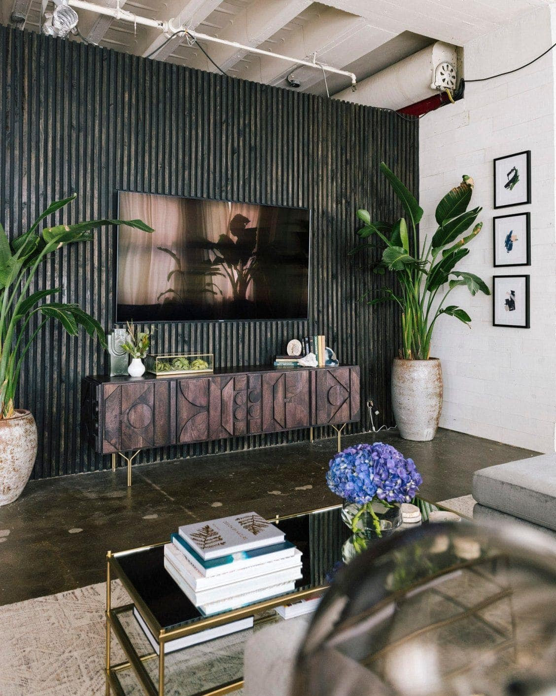 inside the queer eye apartment black feature wall in warehouse living room