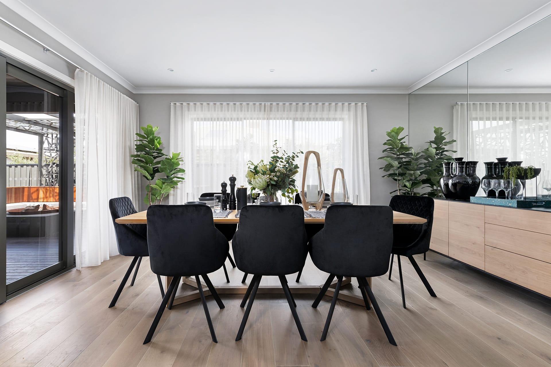 modern dining room with oak timber table and black upholstered dining chairs