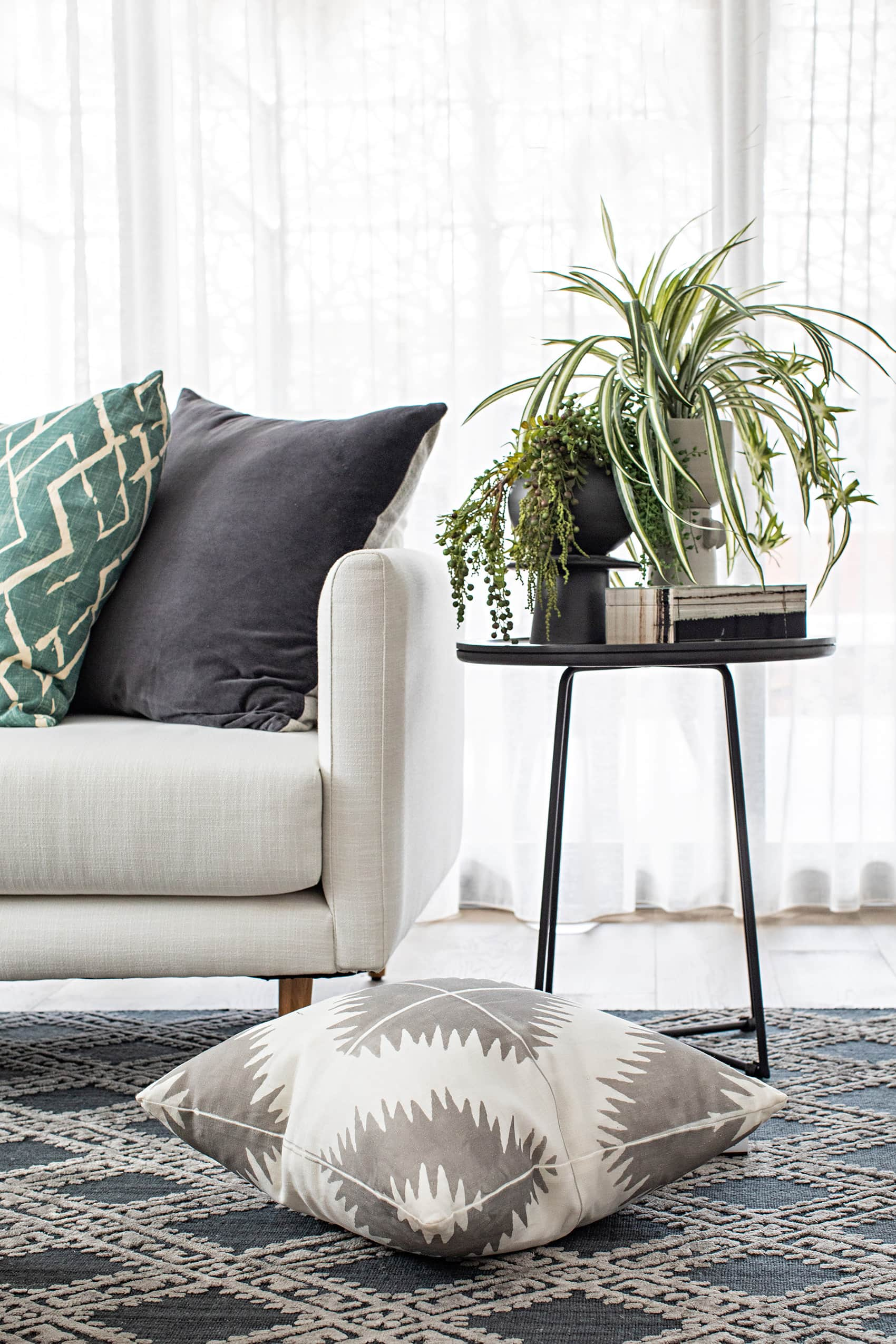round black side table with indoor plants on top and geometric rug
