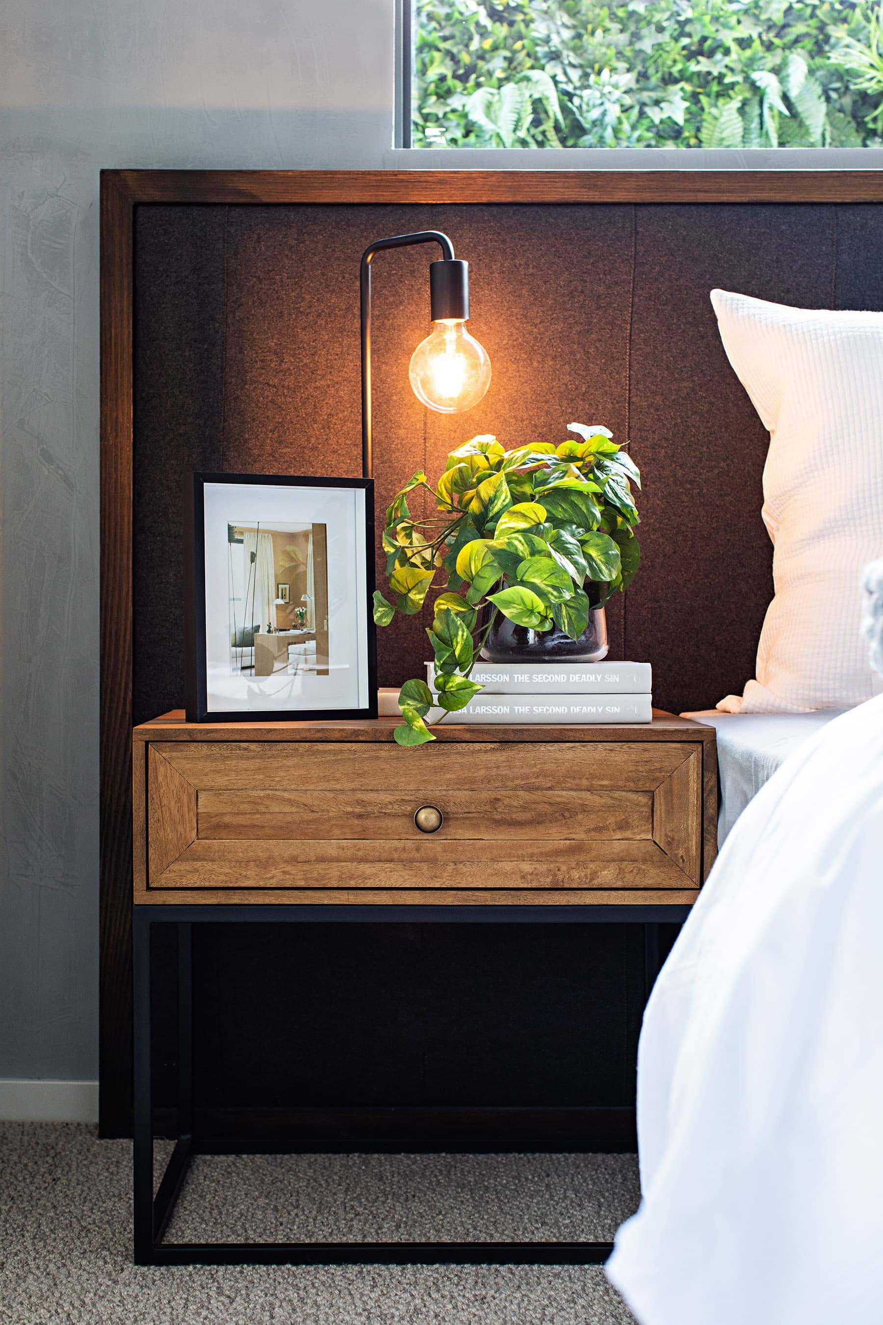 rustic bedside table with indoor plant and stack of books with oversized headboard