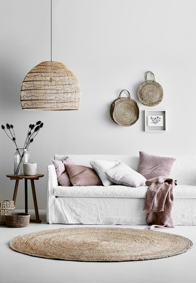 white slip cover sofa with pink velvet cushions from aura home and rattan pendant