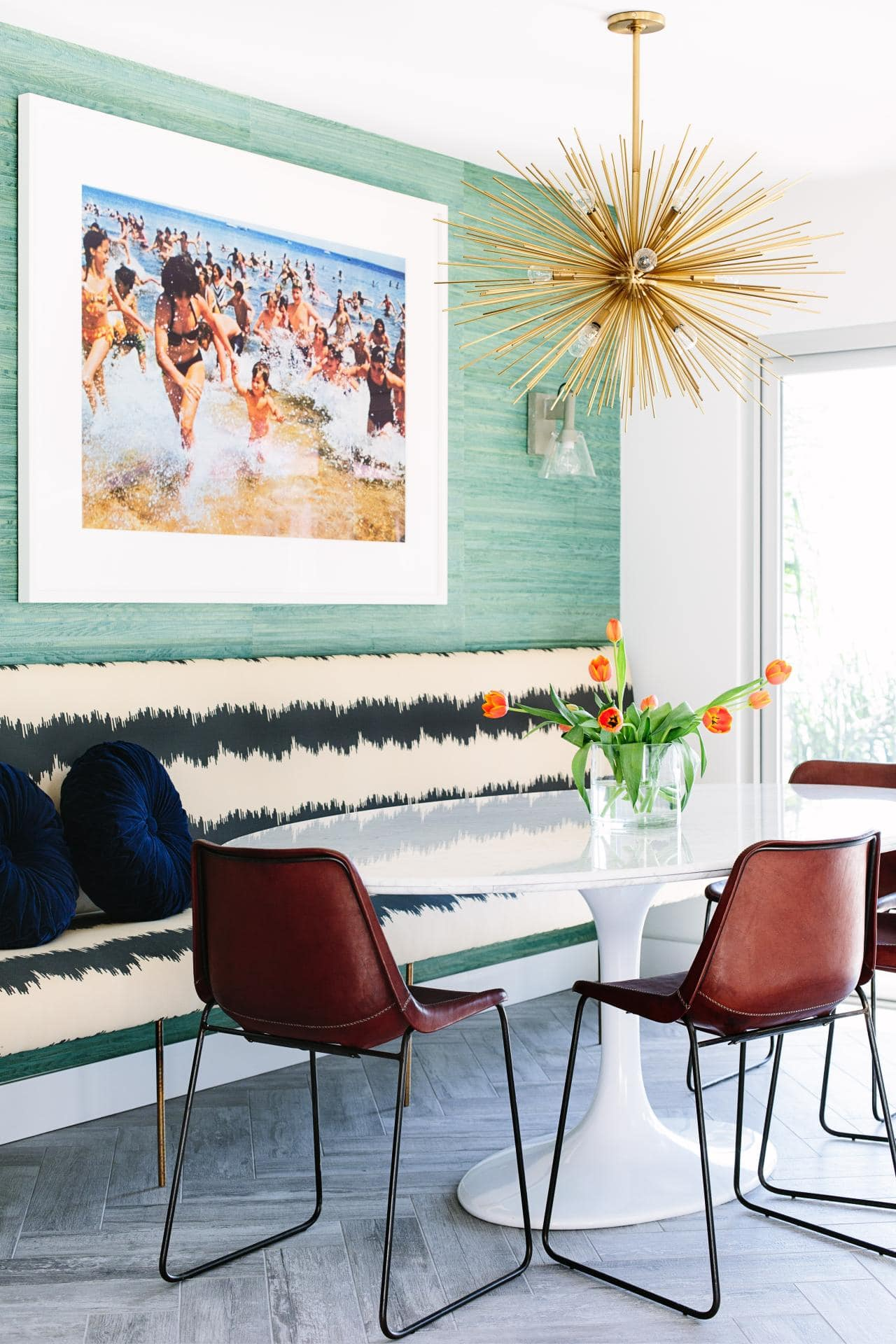banquette seating in dining room with leather dining chairs and green wallpaper