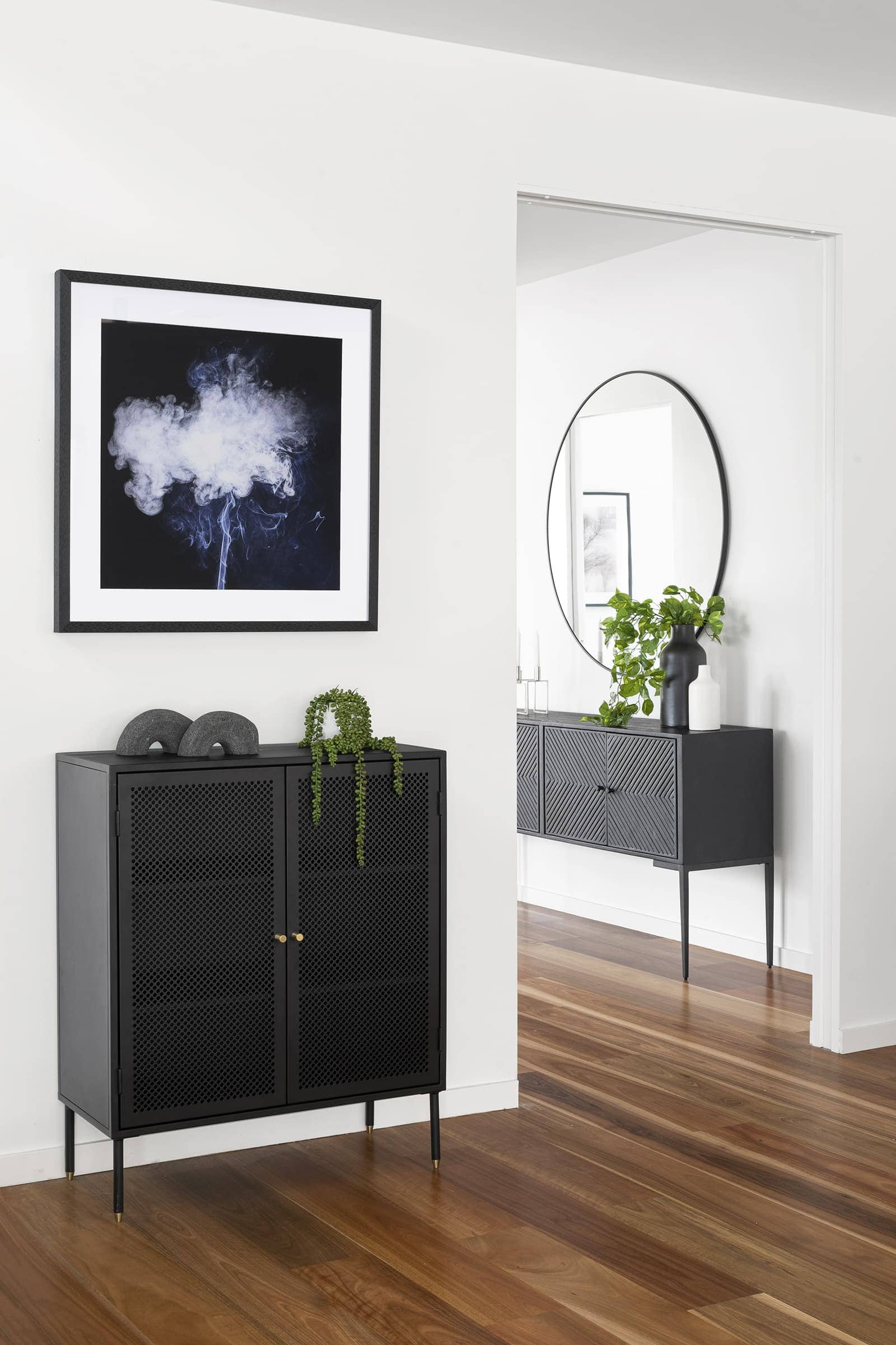 black metal storage unit and black globewest side table in entryway with fake plants